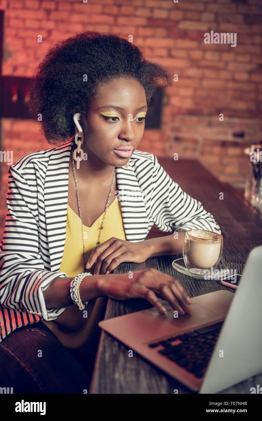 Grave afro-americani di venti anni-vecchia ragazza lavorando sul computer portatile al bancone bar Immagini Stock