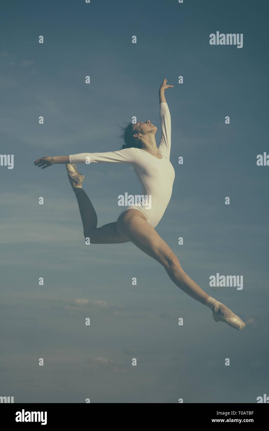 Grazia in ogni mossa. La pratica di arte del balletto classico. Ballerina di saltare sul cielo blu. Carino ballerina. Pretty Woman in ballo l'usura. Classe di balletto Immagini Stock