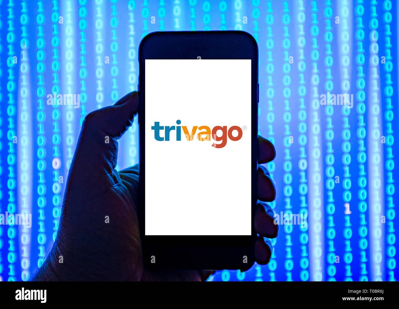 Persona in possesso di smart phone con trivago viaggio sito di confronto logo visualizzato sullo schermo. Immagini Stock