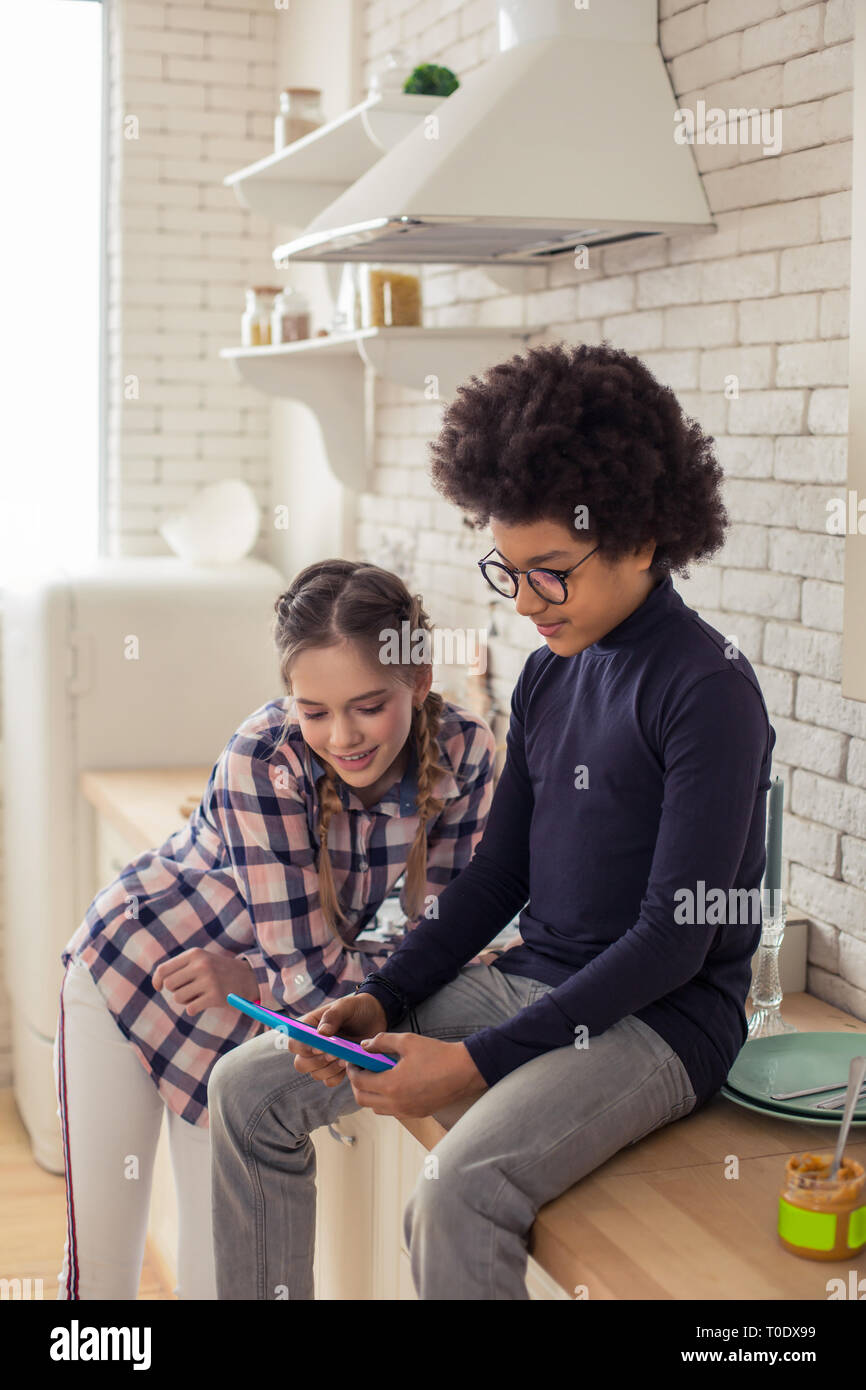 Concentrato di capretto internazionali giocando il gioco online a casa Foto Stock