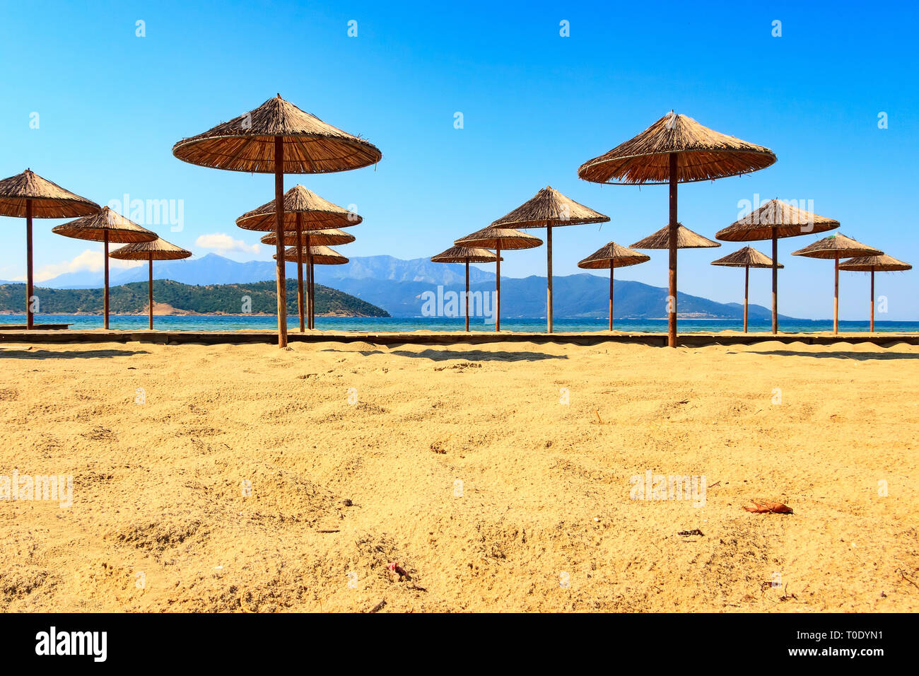 Fila Di Ombrelloni In Legno In Spiaggia Di Sabbia Mare E Cielo Blu