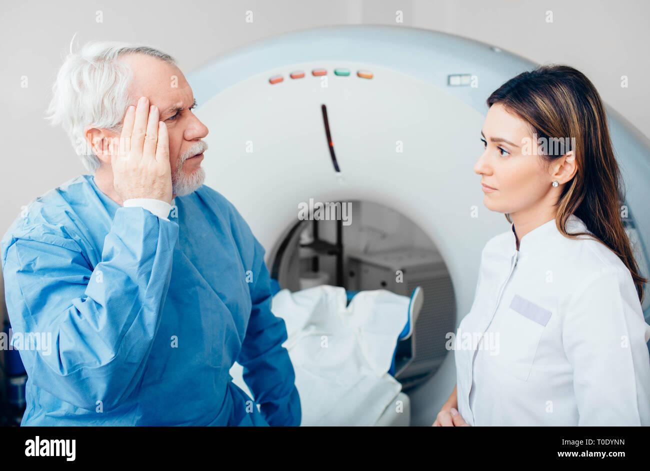 Senior denuncia del paziente di dolore di testa al suo medico mentre è seduto sulla tavola dello scanner. Foto Stock