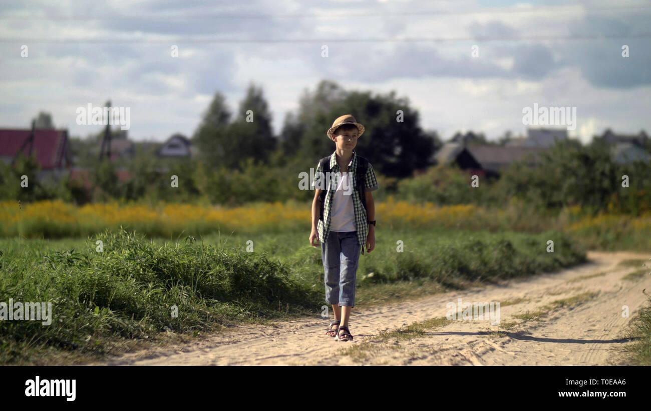 Felice ragazzo viaggi nella campagna circostante Foto Stock