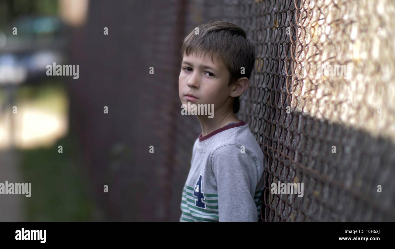 Ragazzo solitario guarda nella telecamera con dolore al volto, rammarico per l'azione Foto Stock
