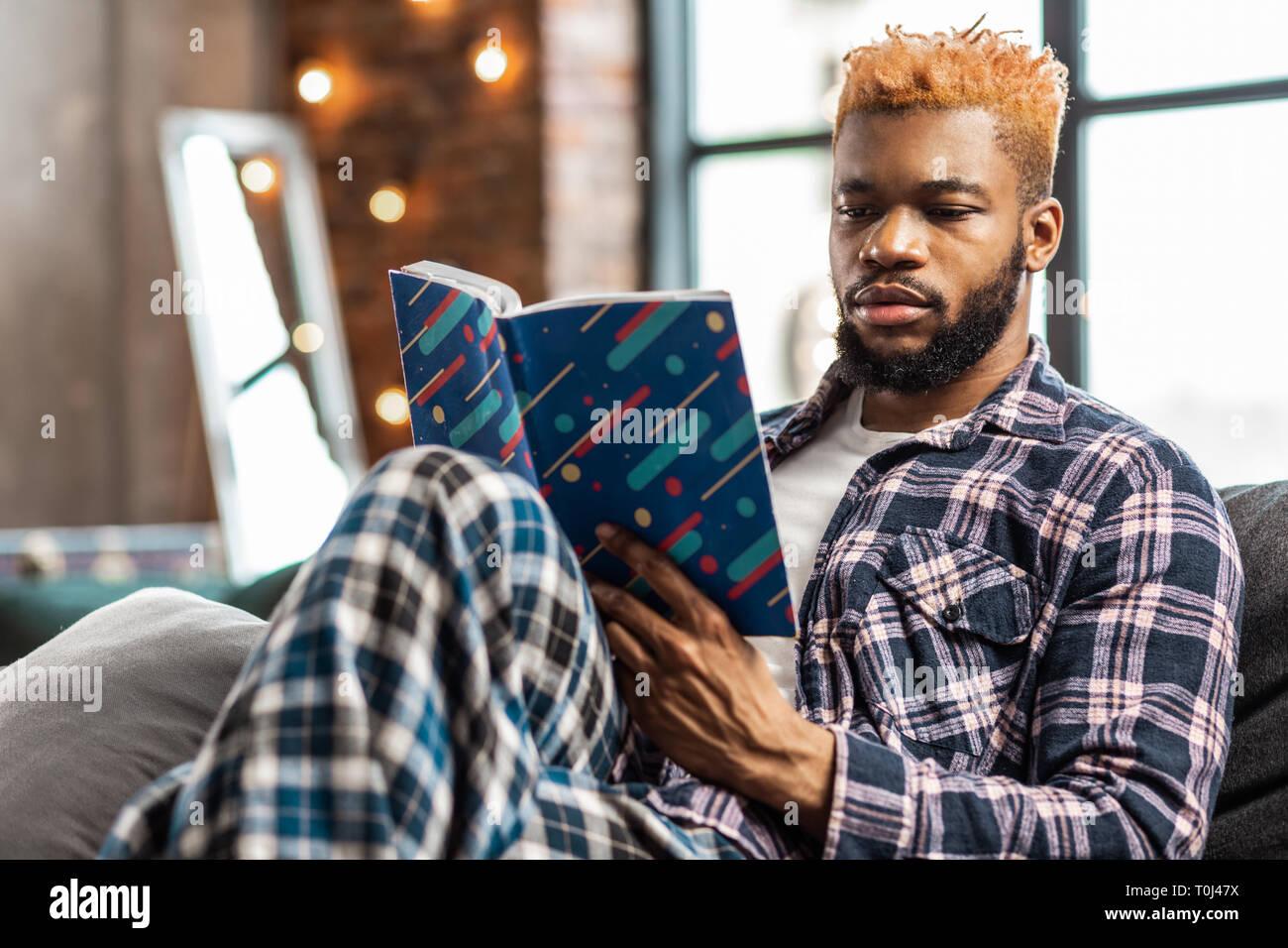Bella buona Cerchi uomo godendo la lettura di un libro Foto Stock
