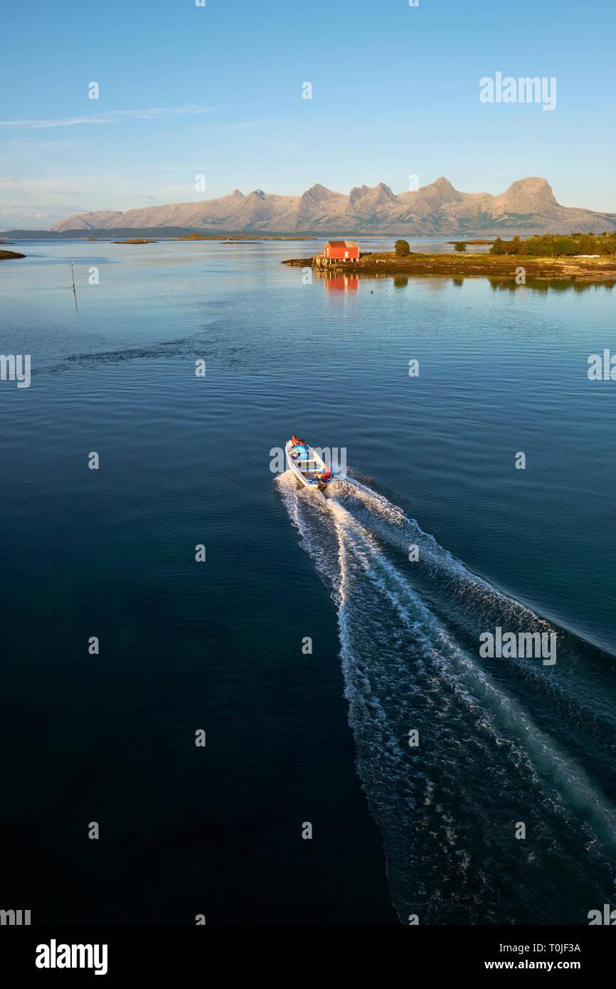 Esplorando le numerose isole e la costa del mare estivo di Heroy E Alsta e la lontana catena montuosa delle sette Sorelle Helgeland Nordland Norvegia Foto Stock