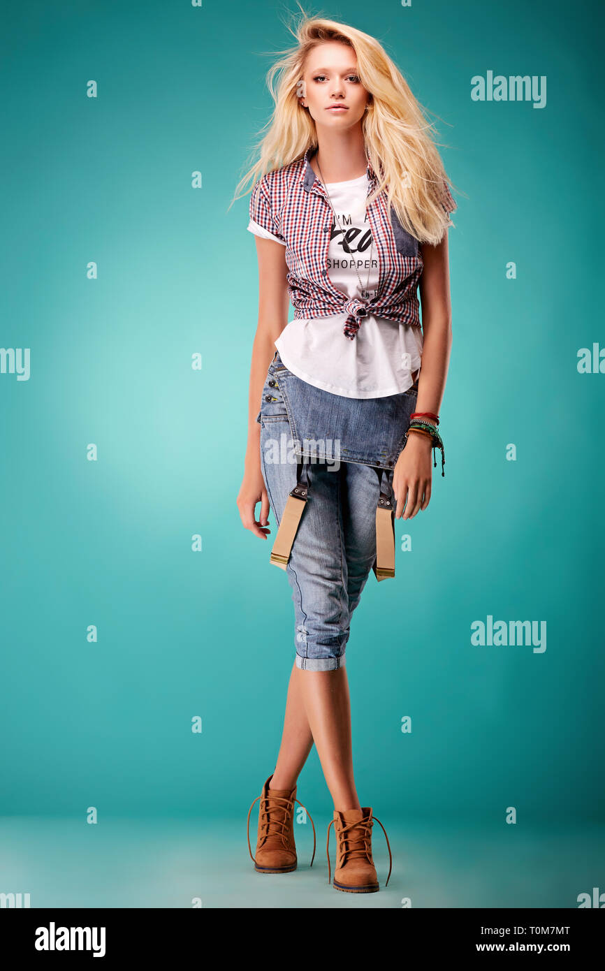 In posa giovane donna in generale alla moda e t-shirt su sfondo blu Immagini Stock