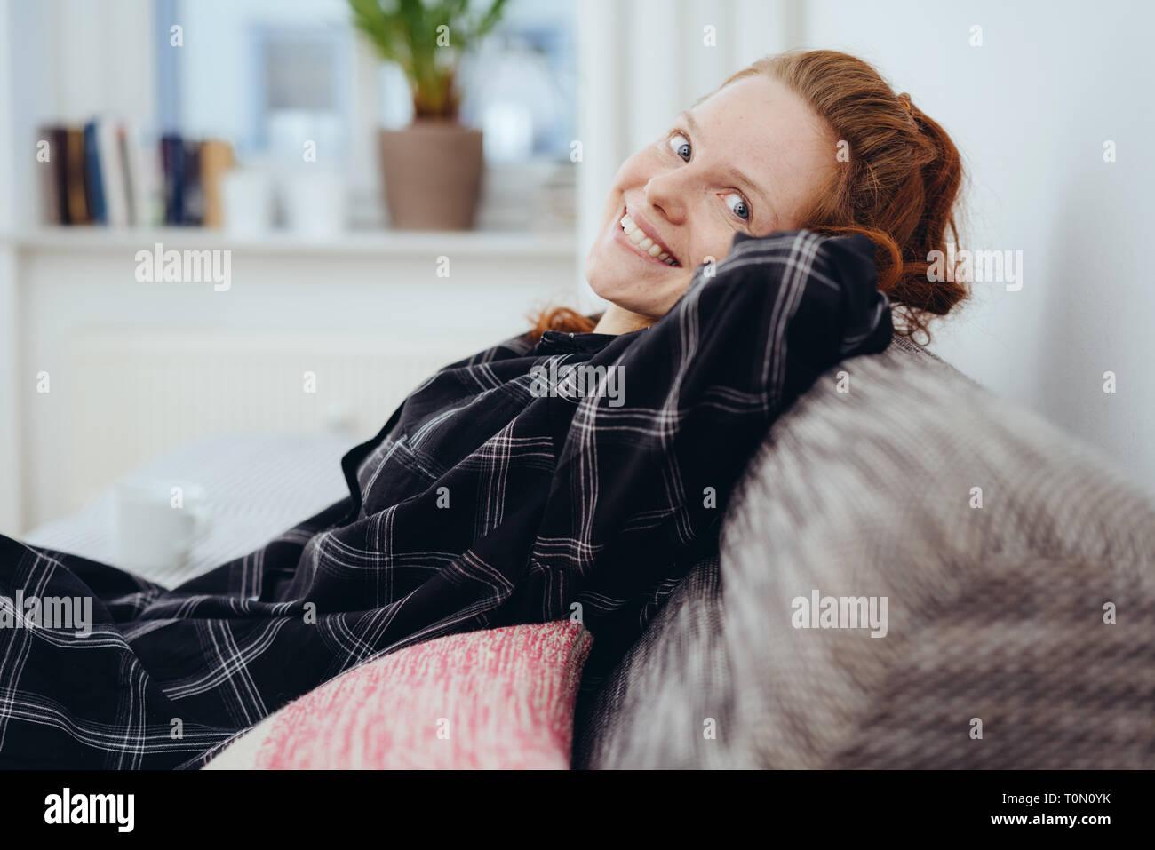 Felice gentile giovane donna redhead relax su un divano svolta a guardare la fotocamera con un bel sorriso caldo Foto Stock