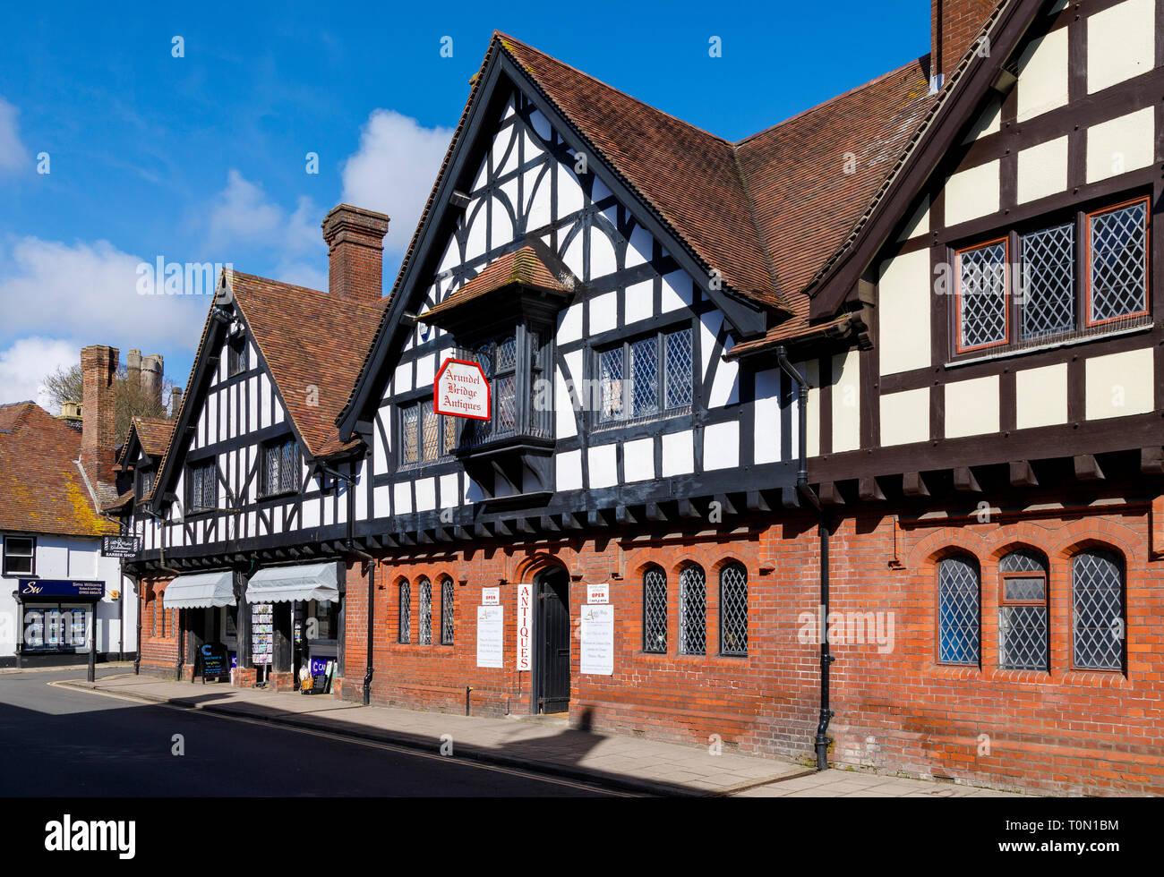 High Street, Arundel, West Sussex. Le aziende entro una metà C19 francone ed edificio di mattoni rossi con finestre al piombo e tetto di tegole. Immagini Stock