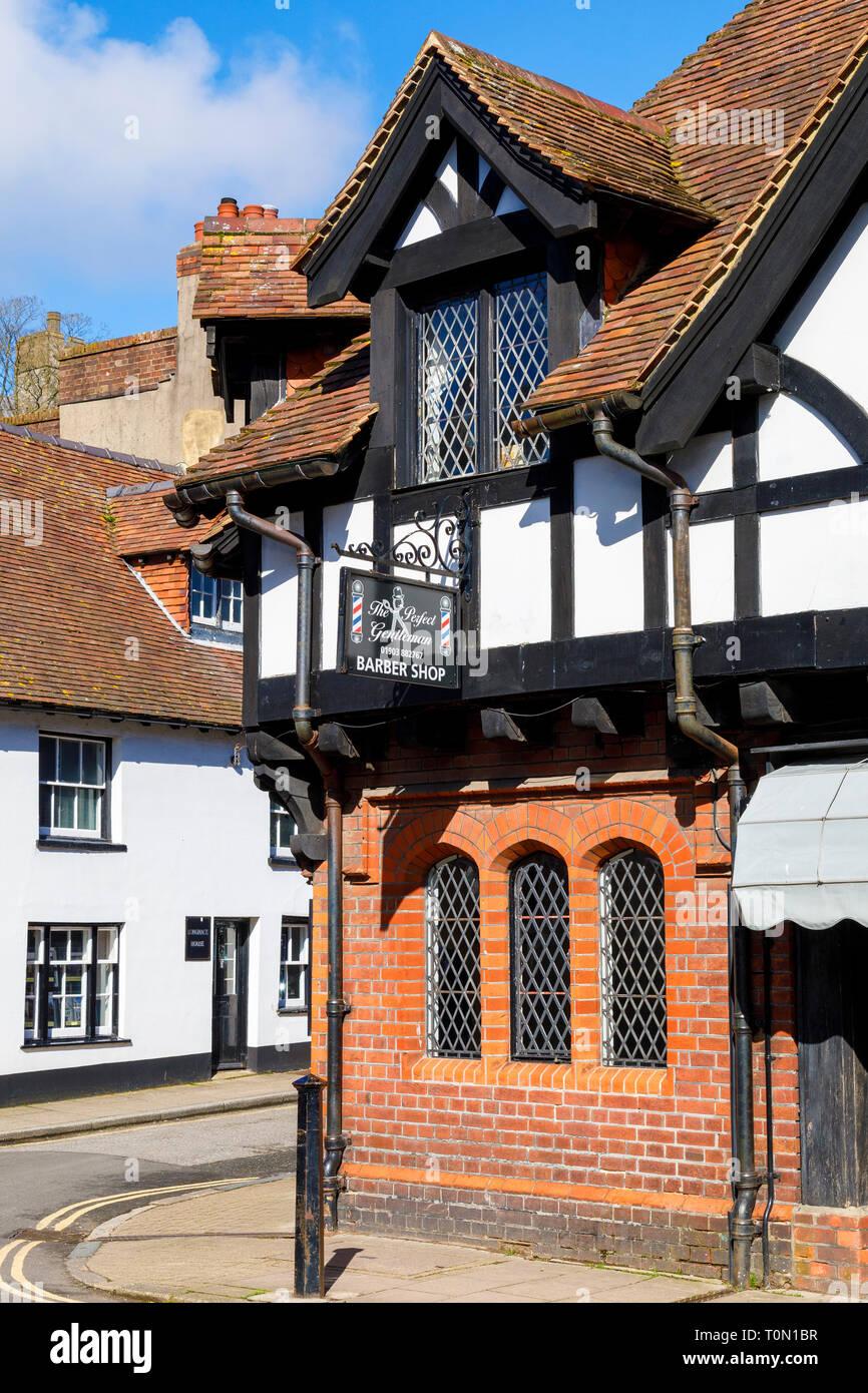 High Street, Arundel, West Sussex. Barber Shop business entro una metà C19 francone ed edificio di mattoni rossi con finestre al piombo e tetto di tegole. Immagini Stock