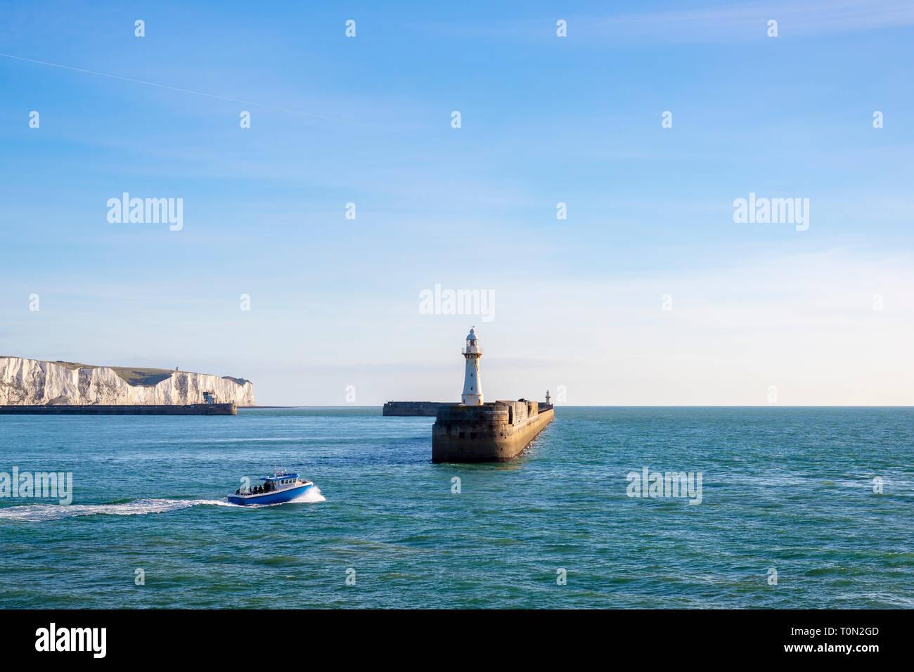 Una barca da pesca di lasciare il porto di Dover; con la mitica Bianche Scogliere in background. Foto Stock
