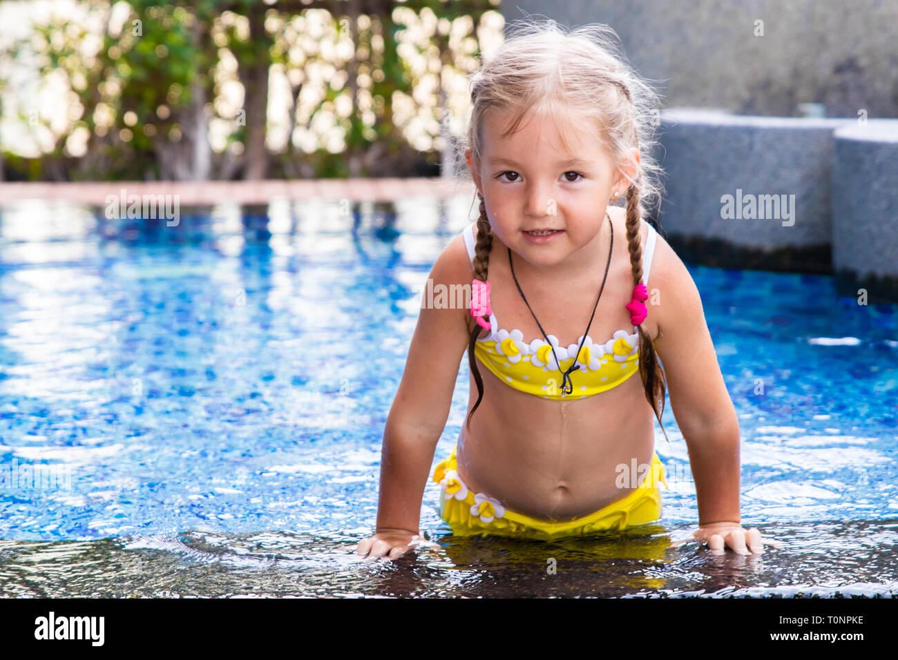 Costumi Da Bagno Per Bambini : Bambina in un giallo costume da bagno in una piscina blu come una