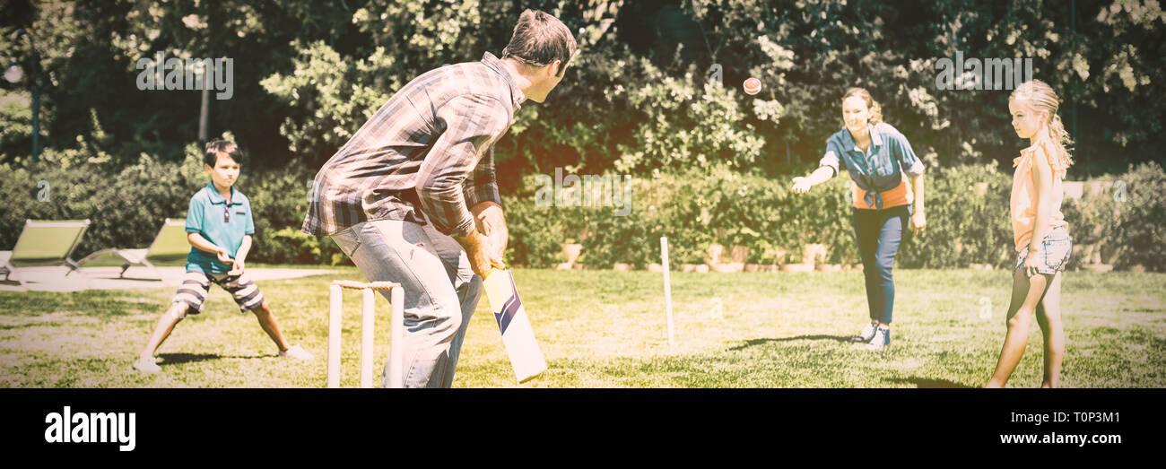 La famiglia felice a giocare a cricket in posizione di parcheggio Foto Stock