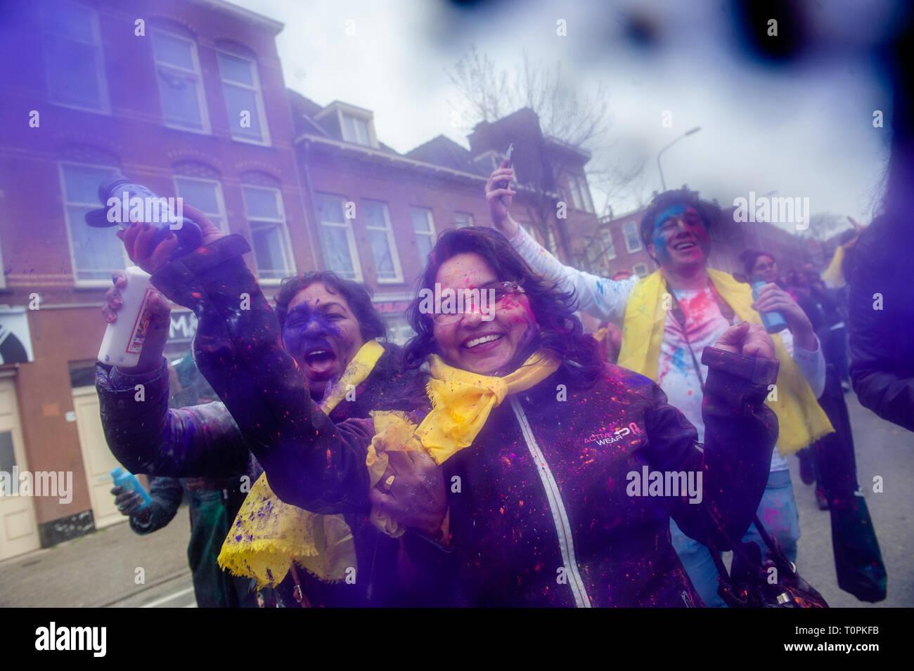 Una donna si vede gettare polvere colorata alla fotocamera durante la celebrazione. Milioni di persone in tutto il mondo celebra la Holi festival Hangámá, noto anche come il Festival dei Colori. Per gli Indù si tratta di una celebrazione dell'arrivo della primavera, il Nuovo Anno e vittoria tutto in uno. La più grande popolazione indiana in Europa (al di fuori del Regno Unito) si trovano all'Aia, questo è uno dei più grandi in Europa. Il clou della festa Holi è la processione attraverso il Transvaal multiculturale e Schilderswijk quartieri. I partecipanti al corteo buttare vivacemente colorato in polvere Foto Stock