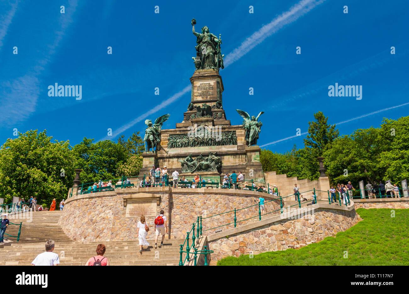Bellissima vista del monumento Niederwalddenkmal in Germania. Ai turisti di ammirare le alte Germania scultura e il grande rilievo al di sotto di esso su un incantevole... Immagini Stock