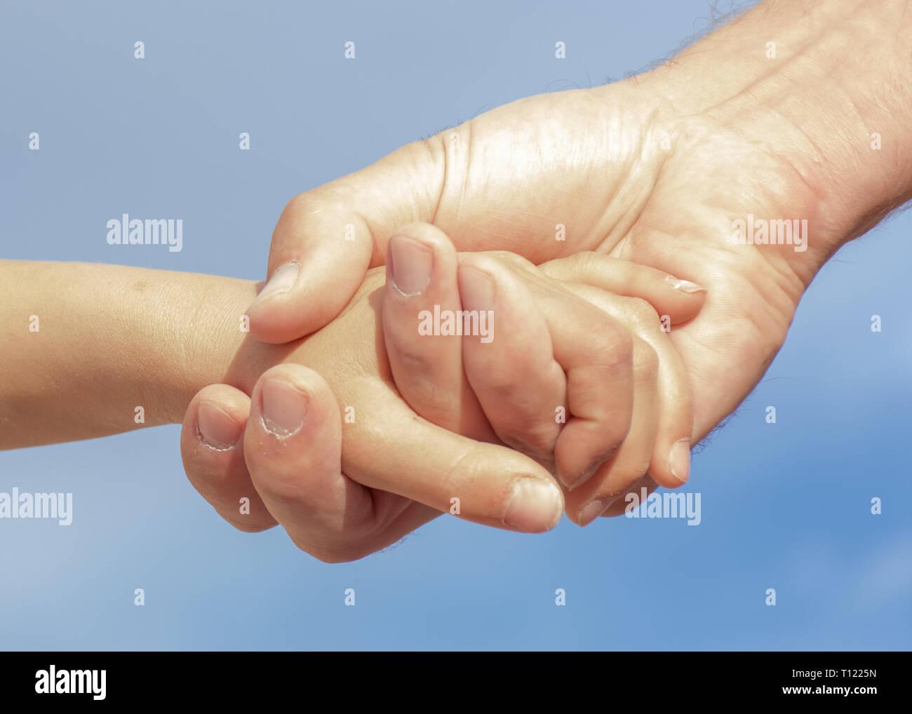 Raggiungere fuori mano nella mano. Un padre a sua figlia tenere le mani con un cielo blu sullo sfondo. Immagini Stock