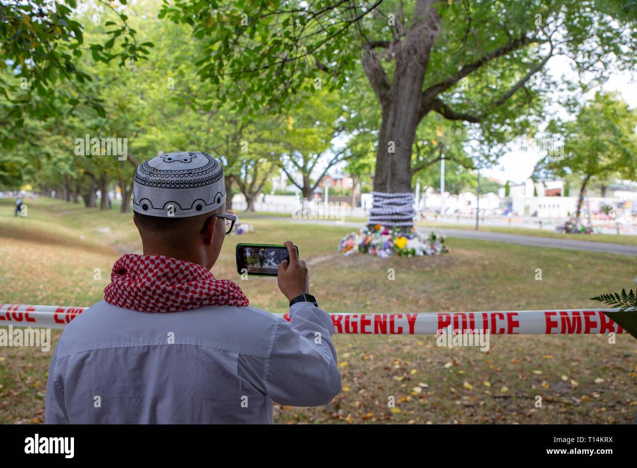 Christchurch, Canterbury, Nuova Zelanda, 22 marzo 2019: un uomo musulmano prende le foto degli omaggi floreali a sinistra nella parte anteriore del Masij Al Noor in simpatia Immagini Stock
