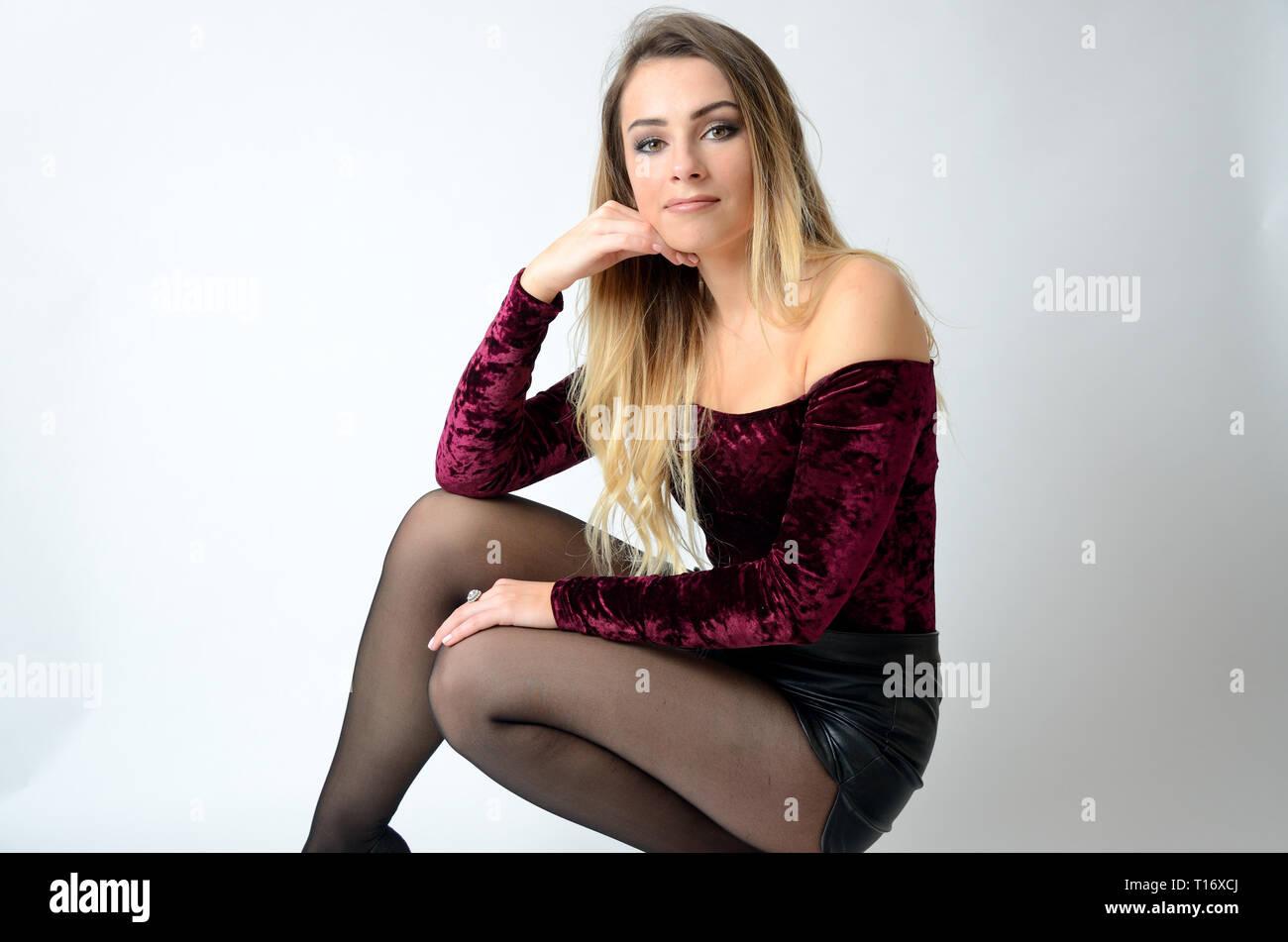 Bellissimo modello polacco. Ben costruita la ragazza con maroon top, pantaloncini neri e calze. Immagini Stock