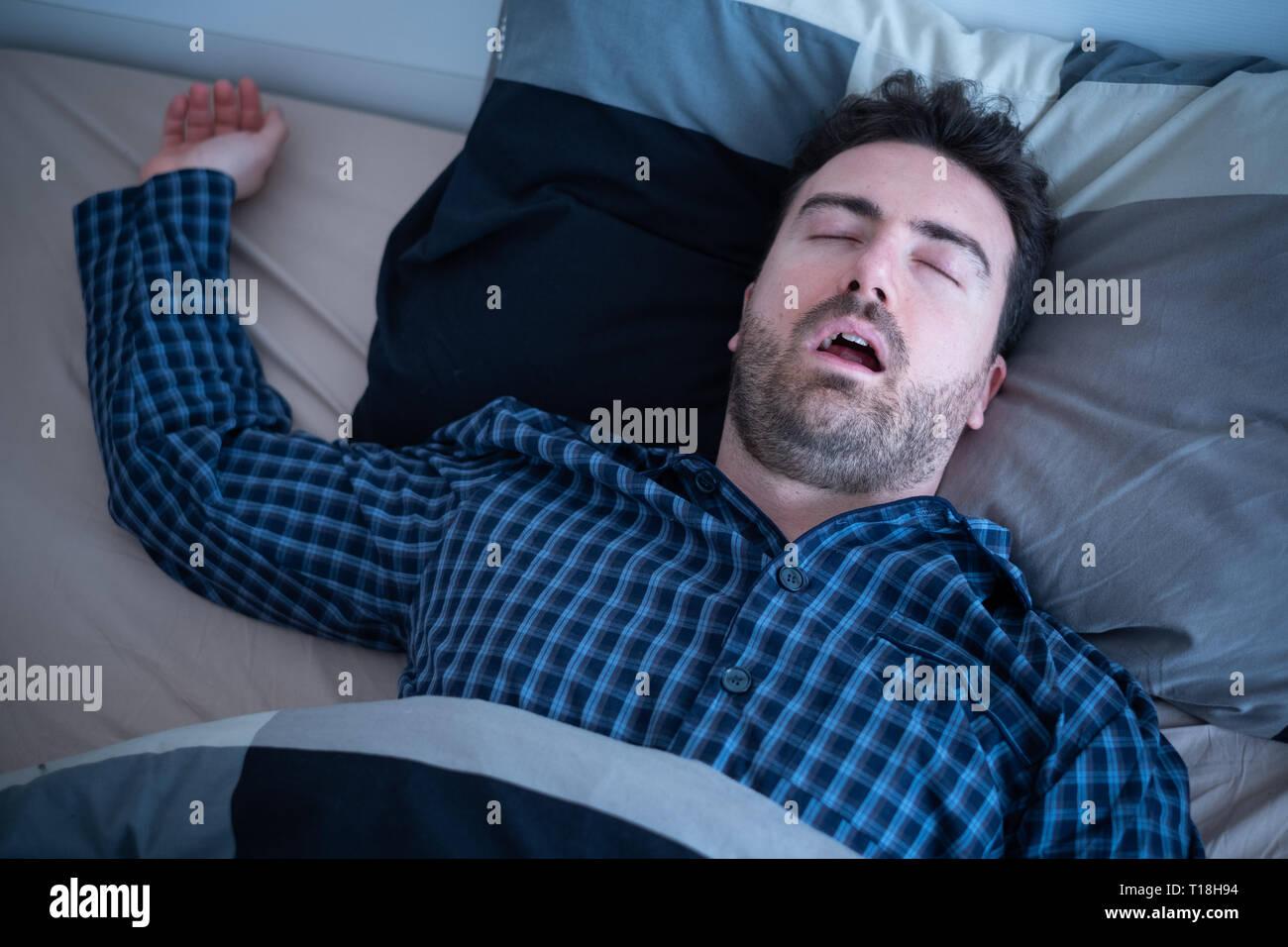 Maschio di sofferenza apnea nel sonno che giace nel letto Immagini Stock