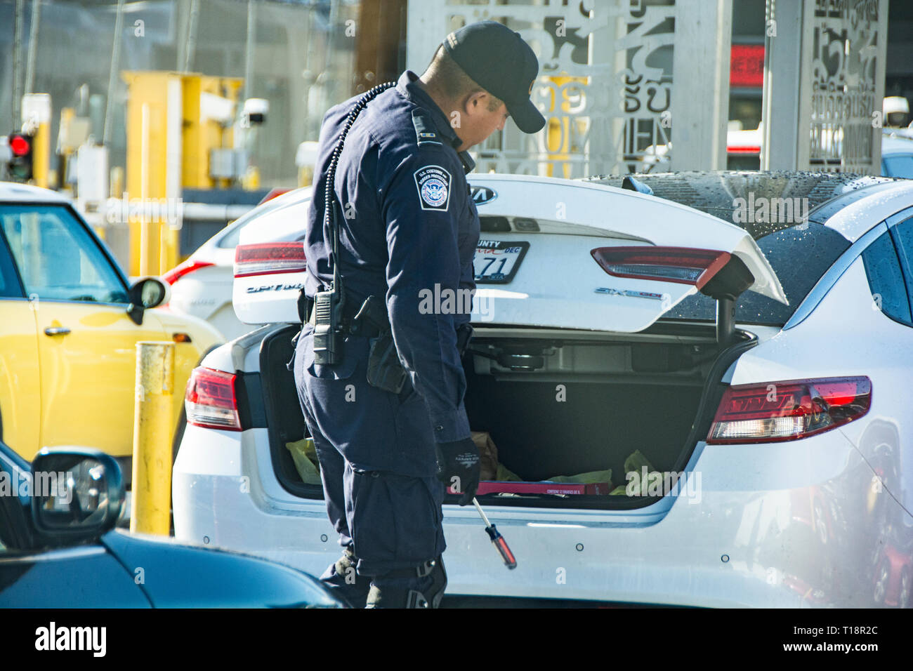 Una pattuglia di confine officer andando auto in auto al San Ysidro di frontiera con uno specchio di peek sotto i veicoli. Immagini Stock
