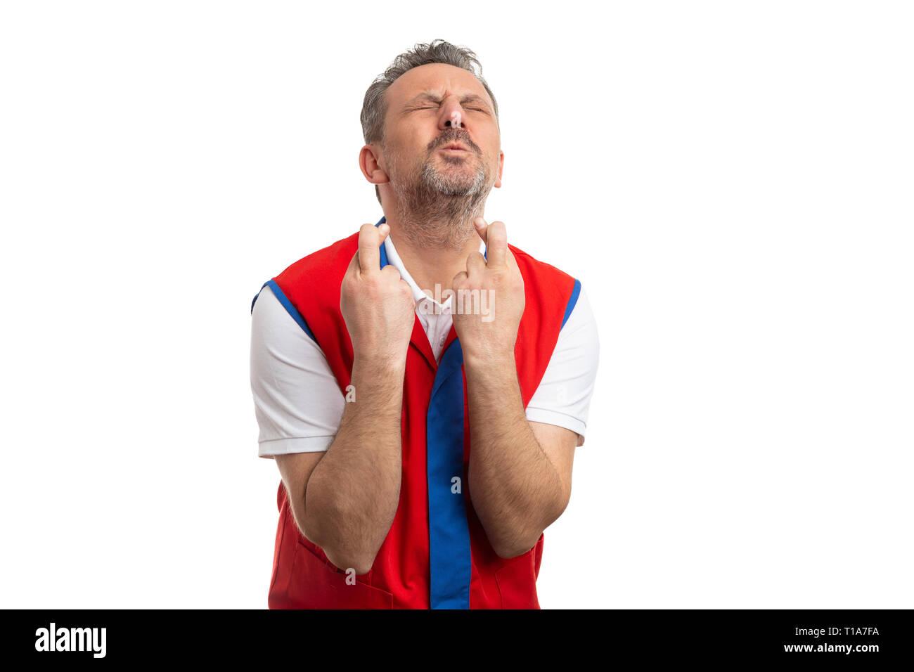 Il supermercato o ipermercato dipendente di sesso maschile come nervoso sperando con le dita incrociate e gli occhi chiusi isolato su bianco di sfondo per studio Immagini Stock