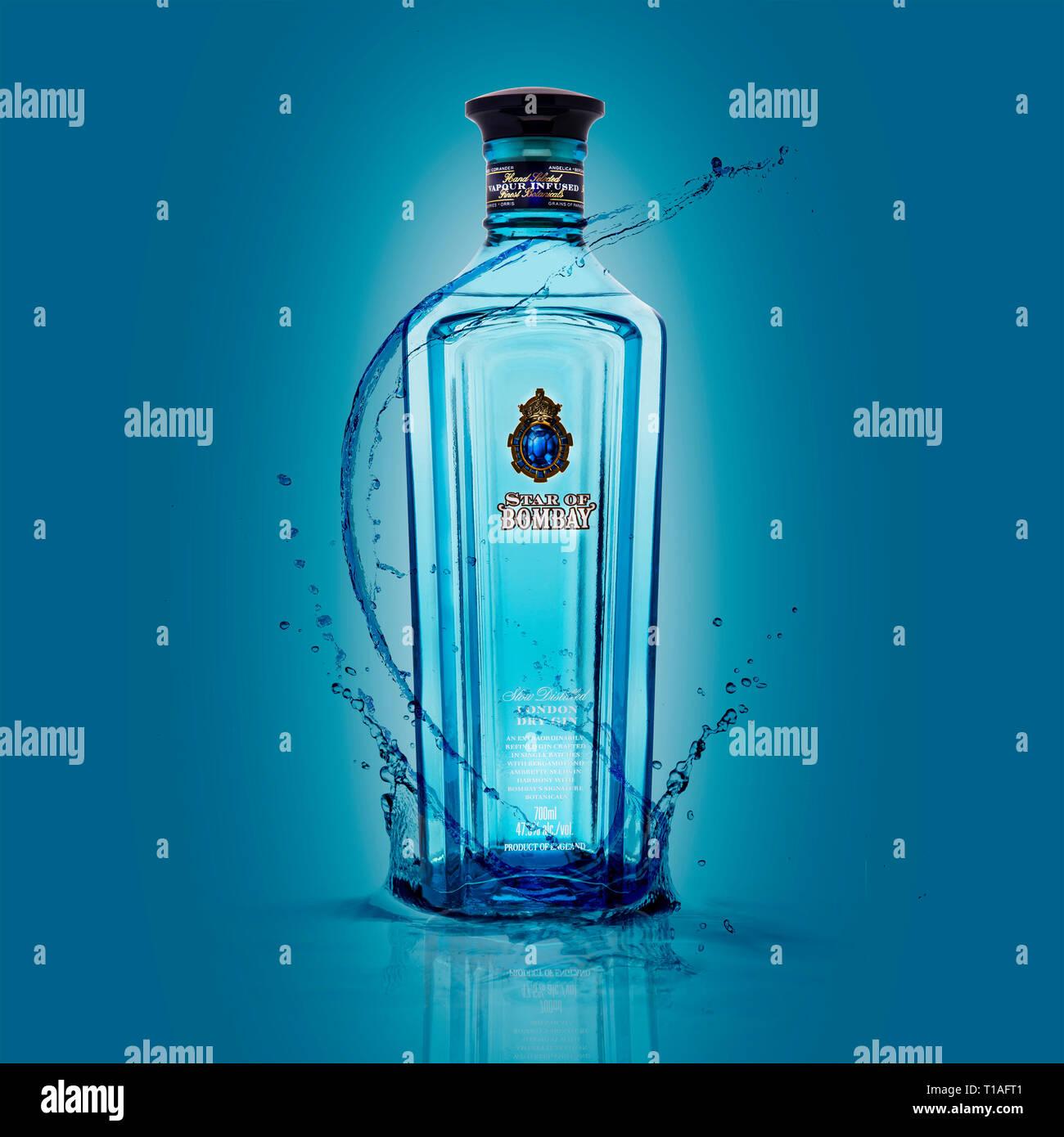 SWINDON, Regno Unito - 24 Marzo 2019: la stella della Bombay London dry gin con spruzzi su uno sfondo blu Immagini Stock