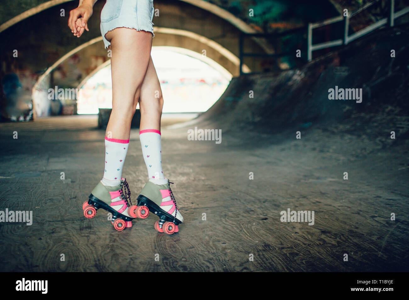 Ben costruita e sottili gambe della ragazza sono illustrati sulla fotocamera. Ella è in piedi sulle sue dita. I rulli sono di colore grigio con rosa. Immagini Stock