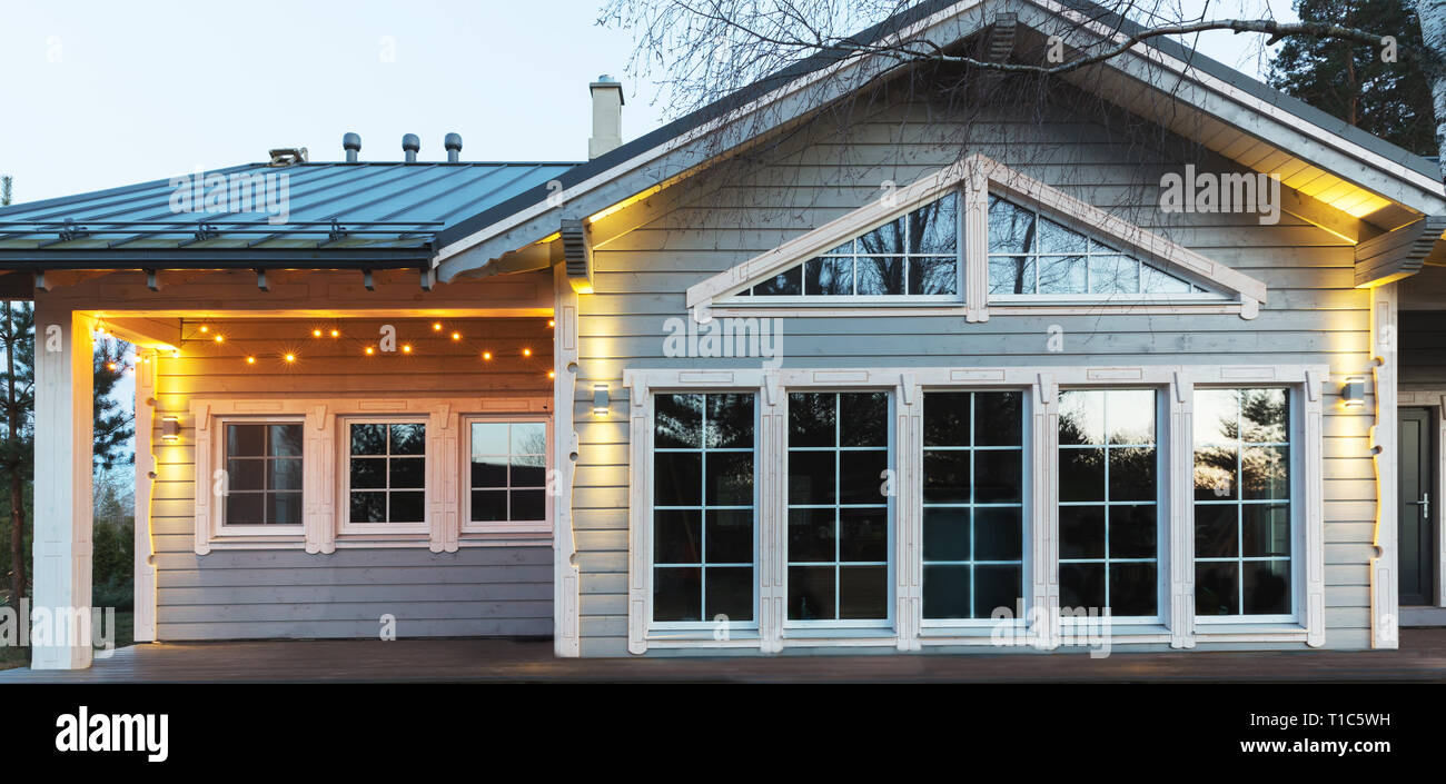 La facciata della grande bella casa in legno con finestre