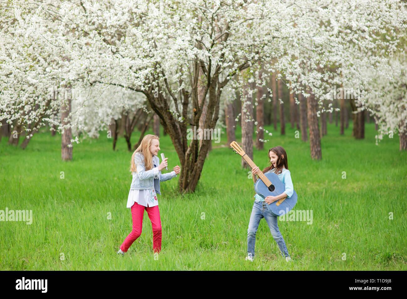 Kids rock band di due divertenti piccole ragazze con chitarra vintage e spazzola per capelli come microfono per riprodurre musica e canto canzone in primavera sbocciano i fiori parco all'aperto Immagini Stock