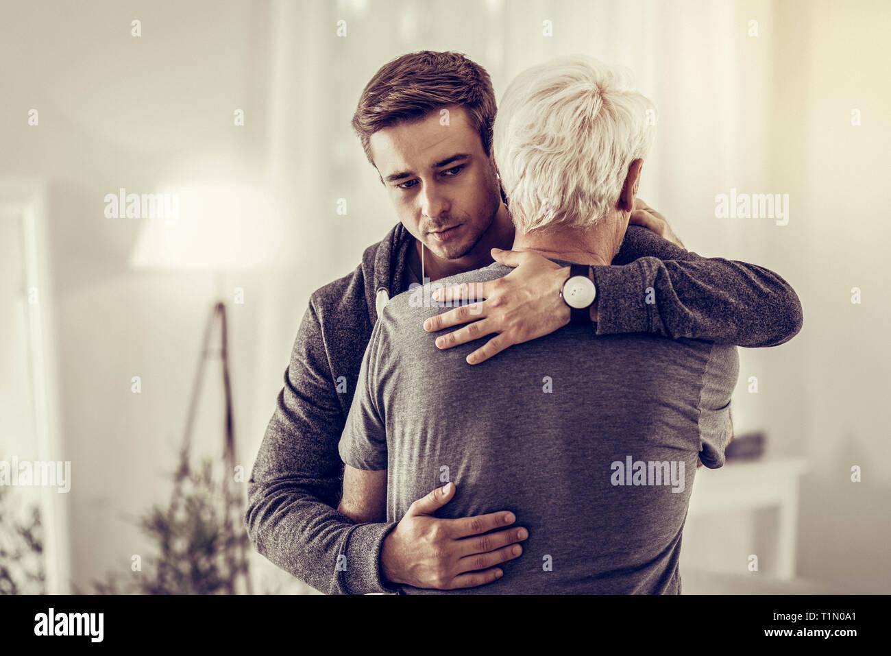 Venti anni dai capelli scuri maschio tipo calmingly cuddling malati doloroso il nonno di invecchiamento Immagini Stock