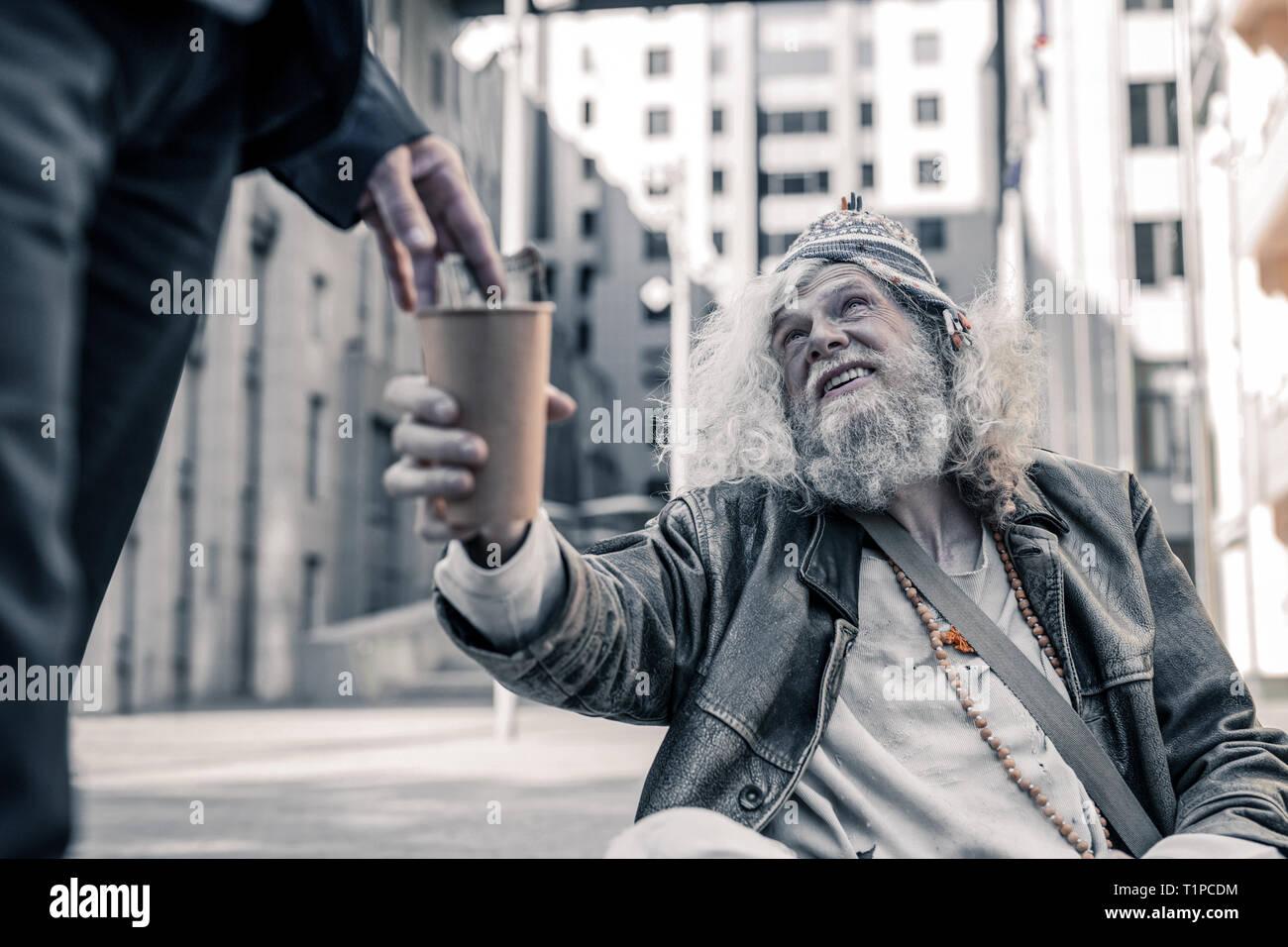 Angustiati dai lunghi capelli uomo essendo poveri senzatetto e raccolta di fondi Immagini Stock