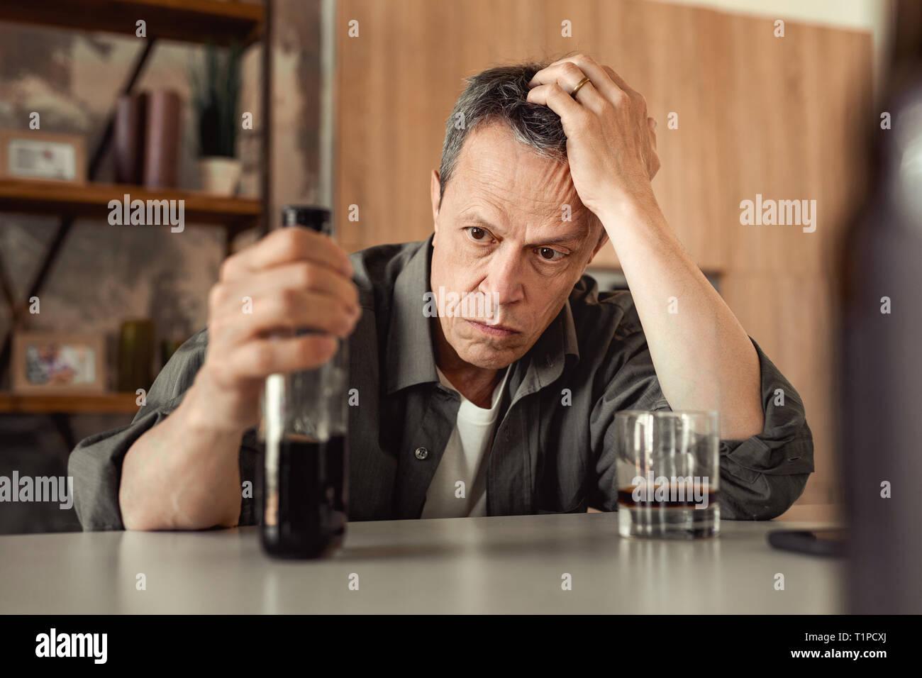 Apatico a pelo corto uomo appoggiato sulla sua mano e portante in parte-bottiglia vuota Immagini Stock