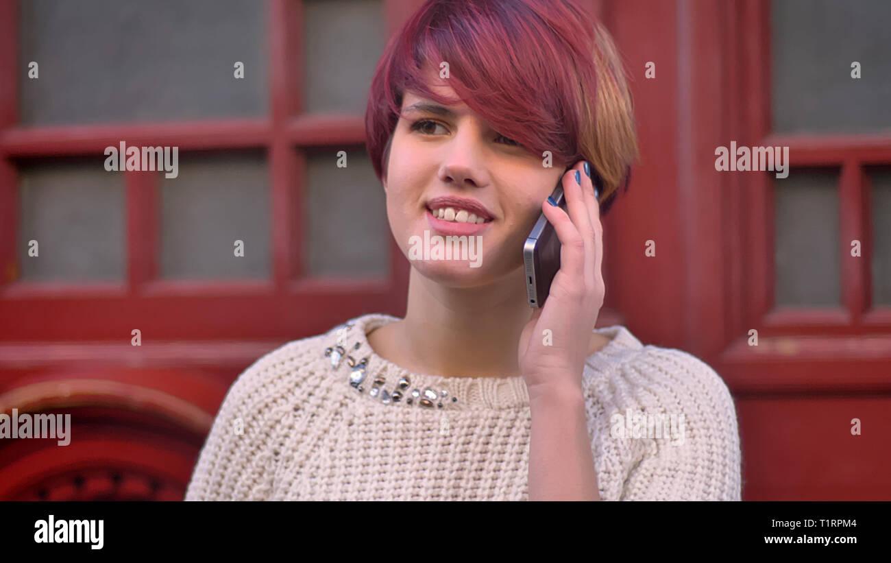 Close-up verticale di concentrato di giovani caucasici-rosa ragazza dai capelli in piedi vicino al red porte e parlando con gioia sul cellulare. Immagini Stock
