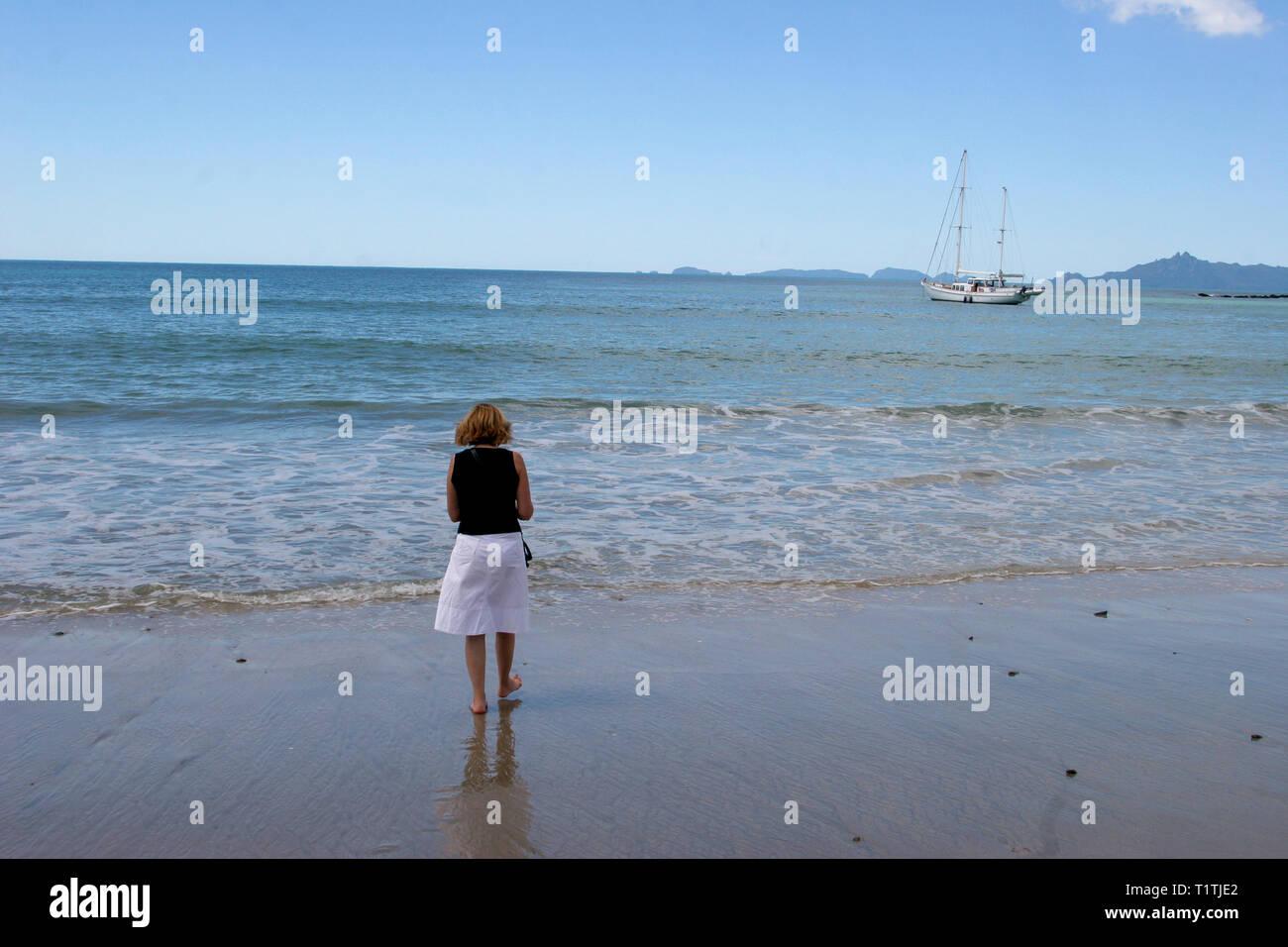 Nuova Zelanda donna alla spiaggia guardando i trend con orizzonte di riferimento e sailingboat per ancora Immagini Stock
