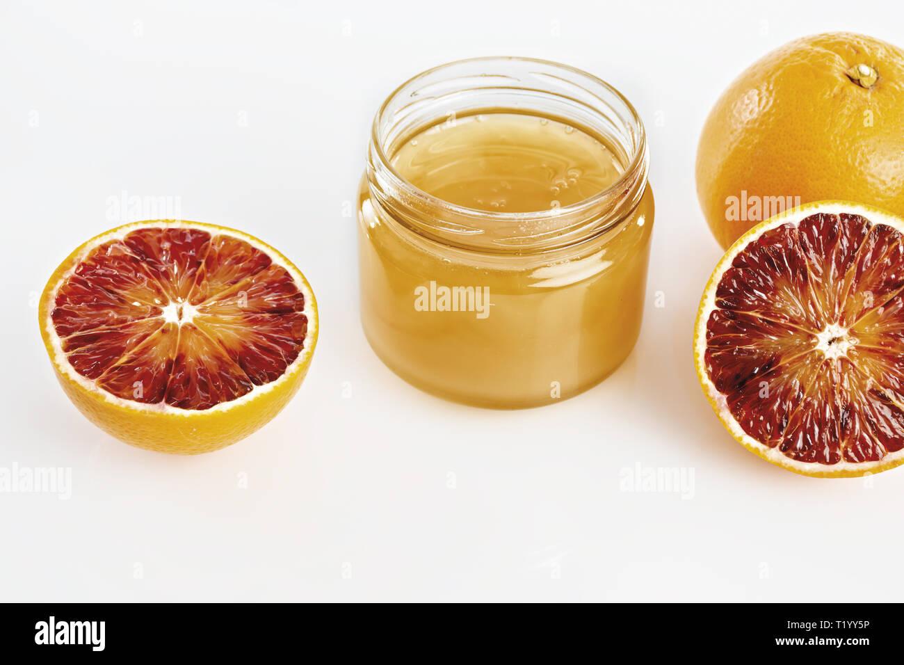 Miele all'arancio in vaso con arance tagliate da sopra Immagini Stock