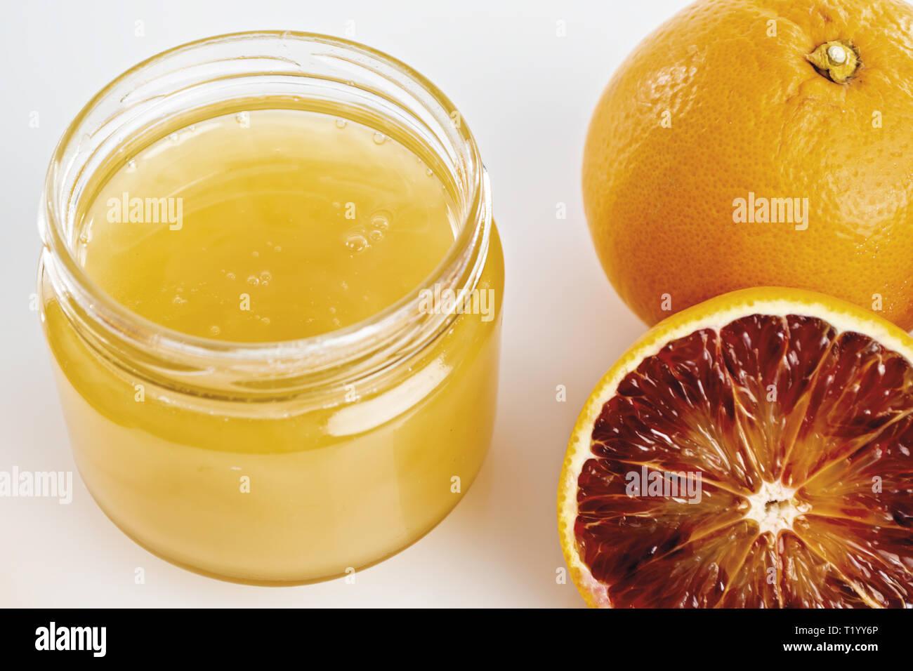 Miele all'arancio in vaso con arance tagliate da sopra. primo piano Immagini Stock
