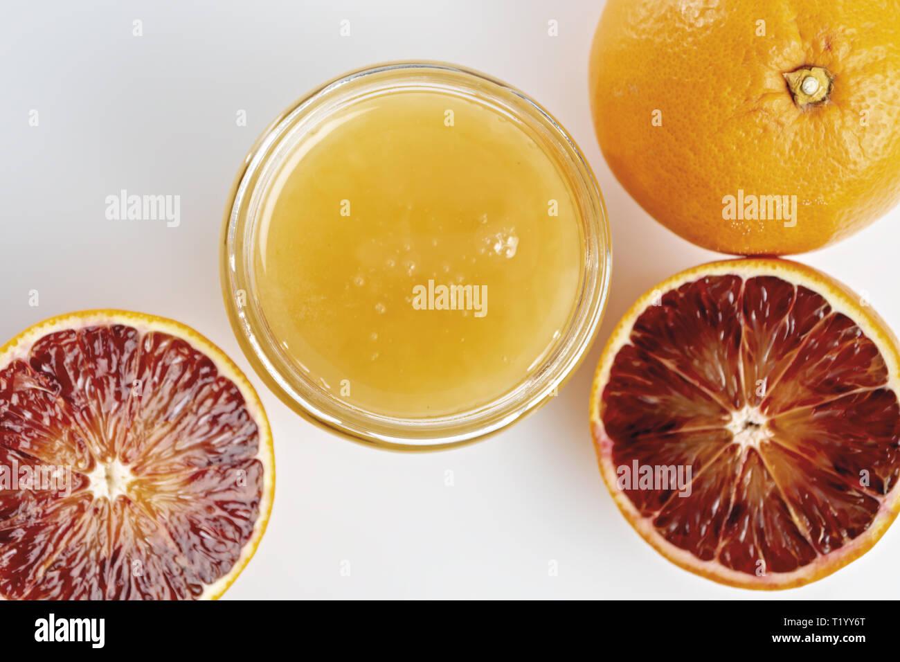 Miele all'arancio in vaso con arance tagliate dall'alto. primo piano Immagini Stock