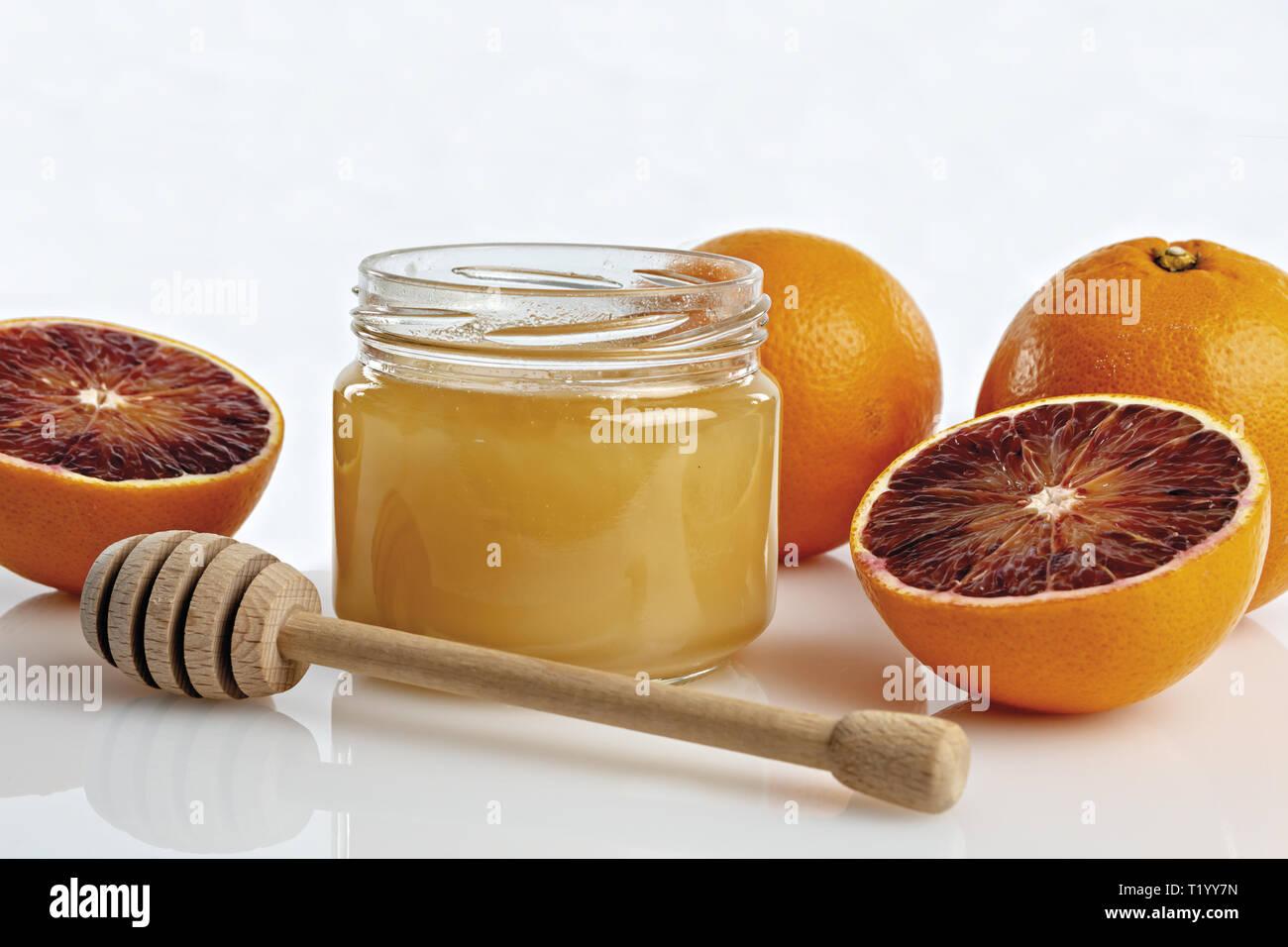 Miele all'arancio in vaso con arance tagliate. primo piano con cucchiaio Immagini Stock