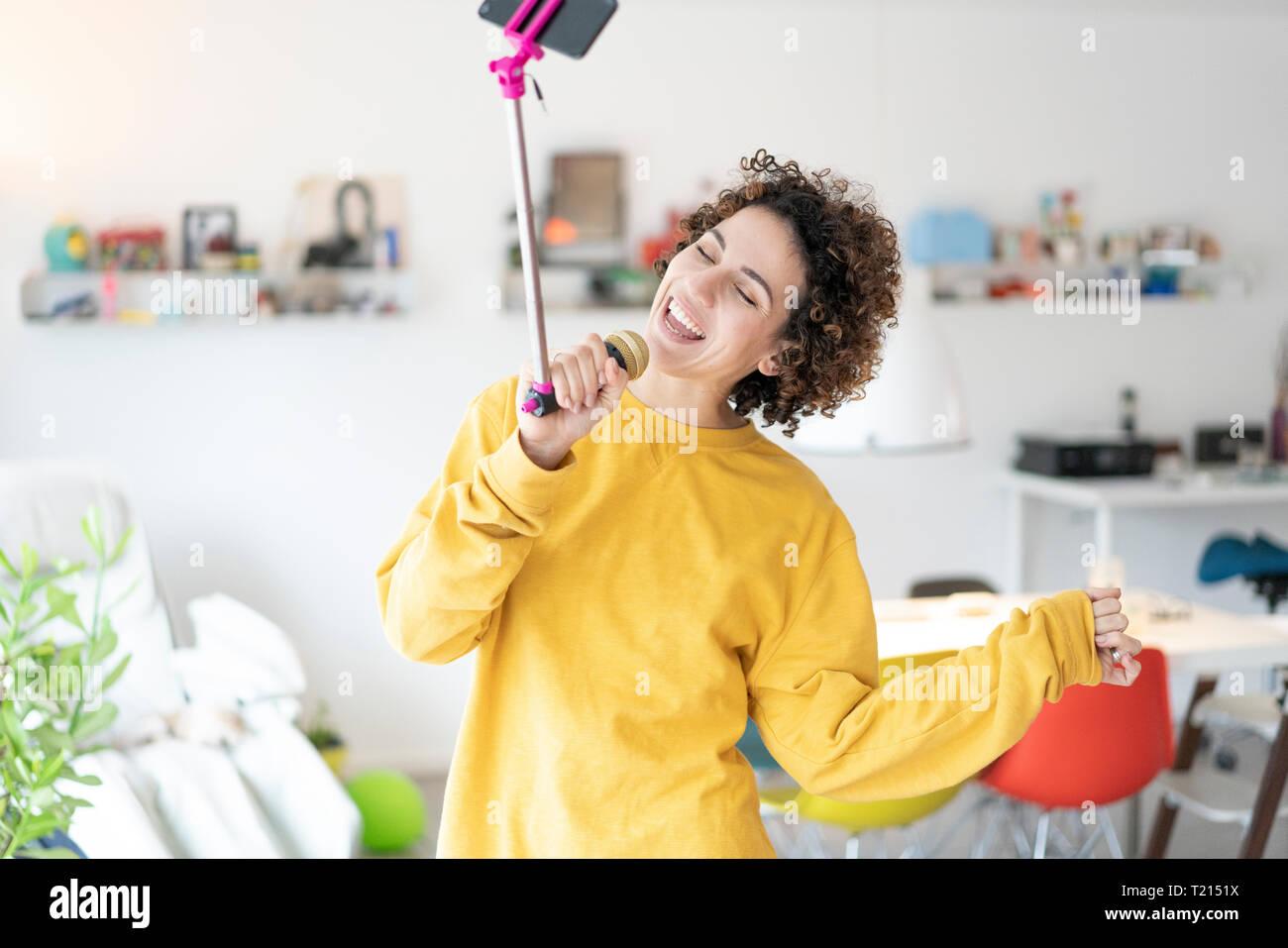 Carefree donna a casa a cantare nel microfono attaccato ad un bastone selfie Immagini Stock