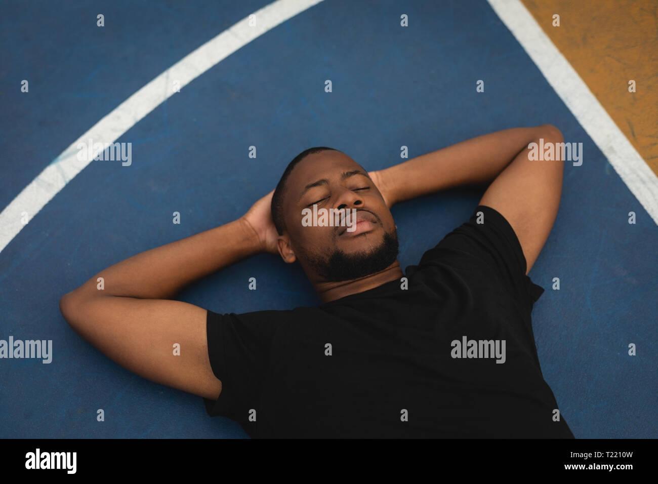 Giocatore di basket rilassante sul pavimento nel campo di pallacanestro Foto Stock