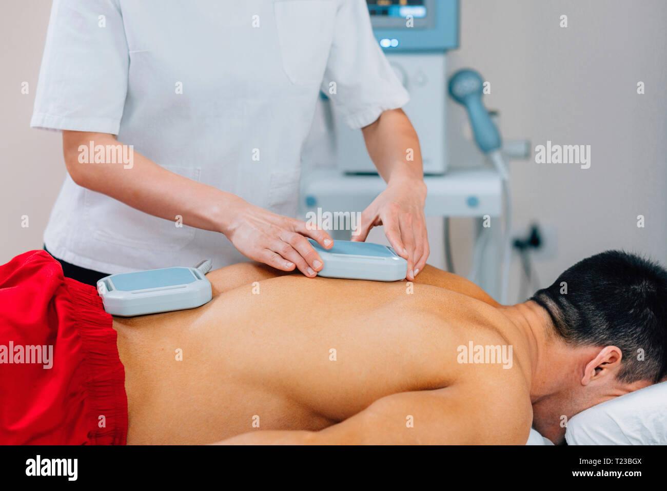 Magnetoterapia. Fisioterapista immissione magneti sulla schiena del paziente. Foto Stock