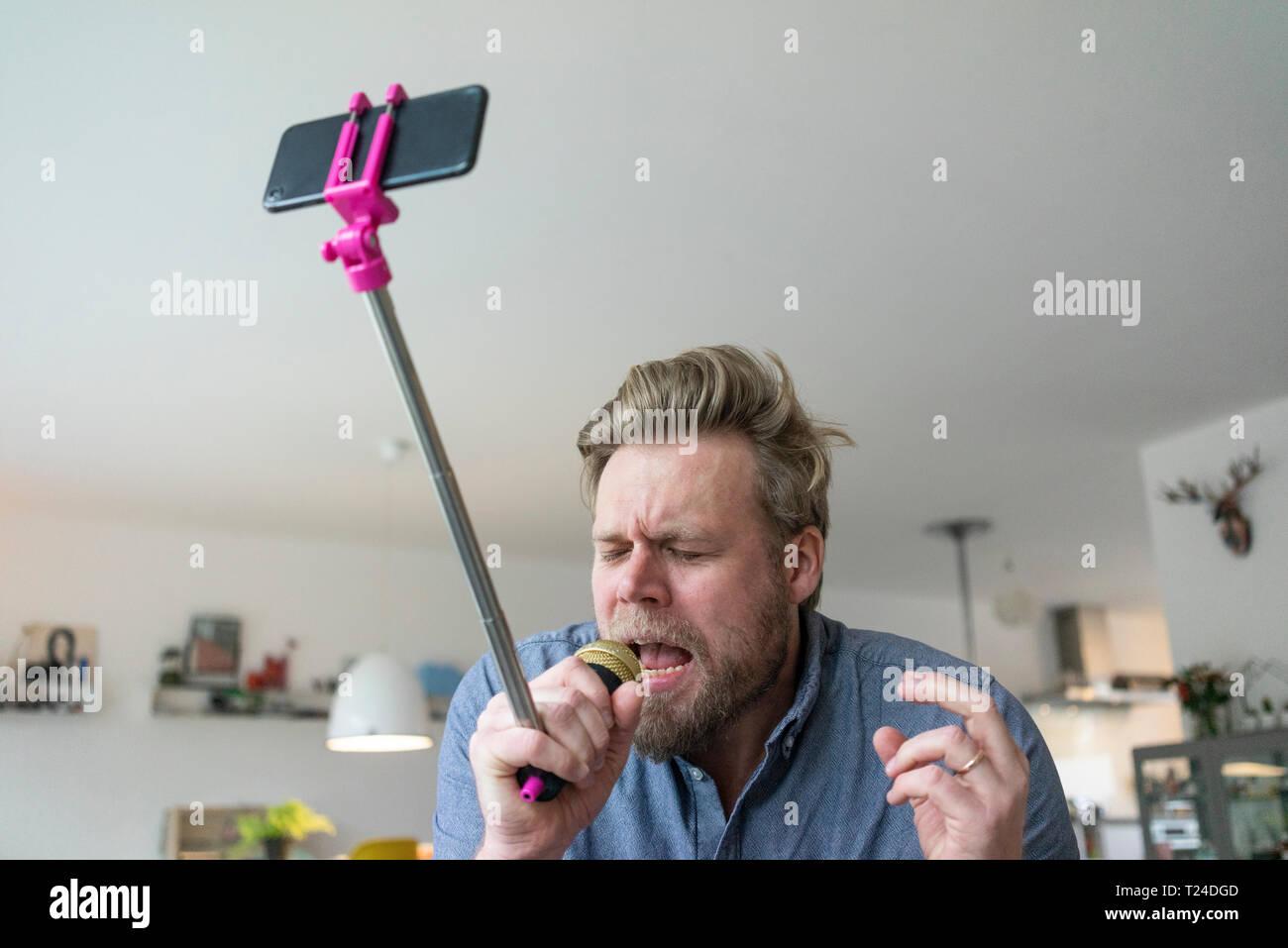 Uomo a casa a cantare nel microfono attaccato ad un bastone selfie Immagini Stock
