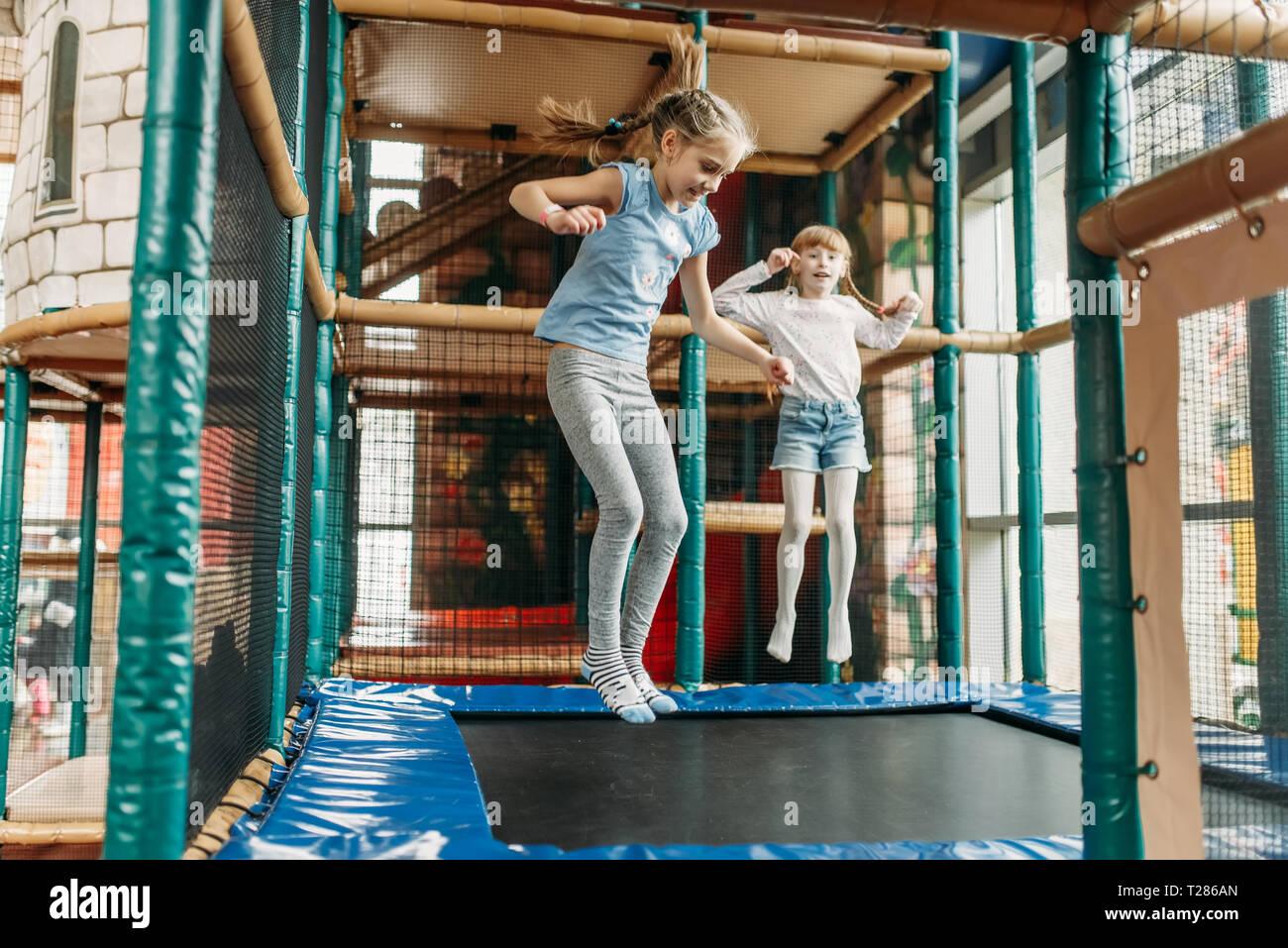 Due ragazze divertente saltando sul trampolino, bambini Game center. Emozionato i bambini divertirsi sul parco giochi al chiuso. Bambini che giocano nel centro di divertimenti Immagini Stock