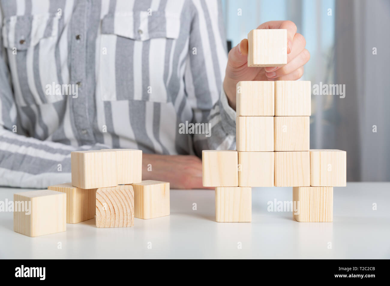 Donna immissione ultimo pezzo per blocchi di legno nella forma di un razzo. Start up avvio del business il concetto di successo Foto Stock