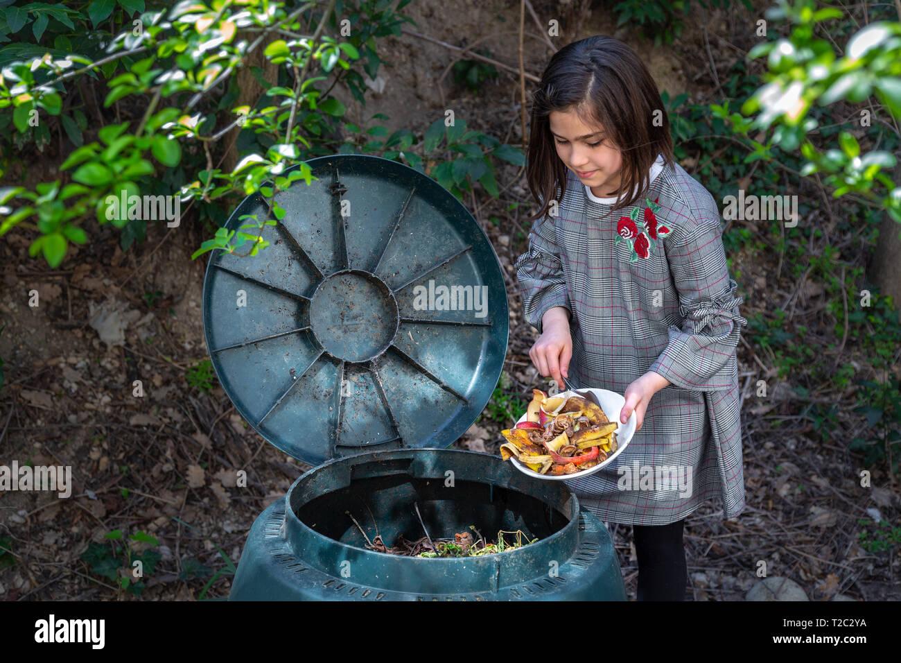 Età primaria i bambini lo svuotamento di residui di alimenti in un compost bin Immagini Stock