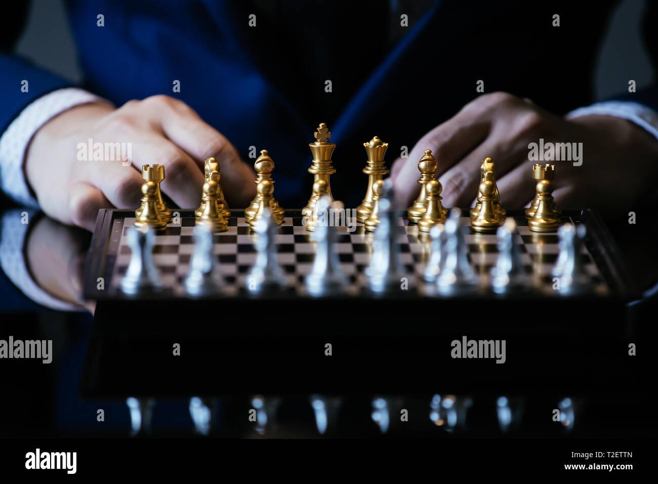 Immagine ritagliata di imprenditore in tuta di pensare sul movimento mentre è seduto al tavolo di vetro e giocare a scacchi Foto Stock