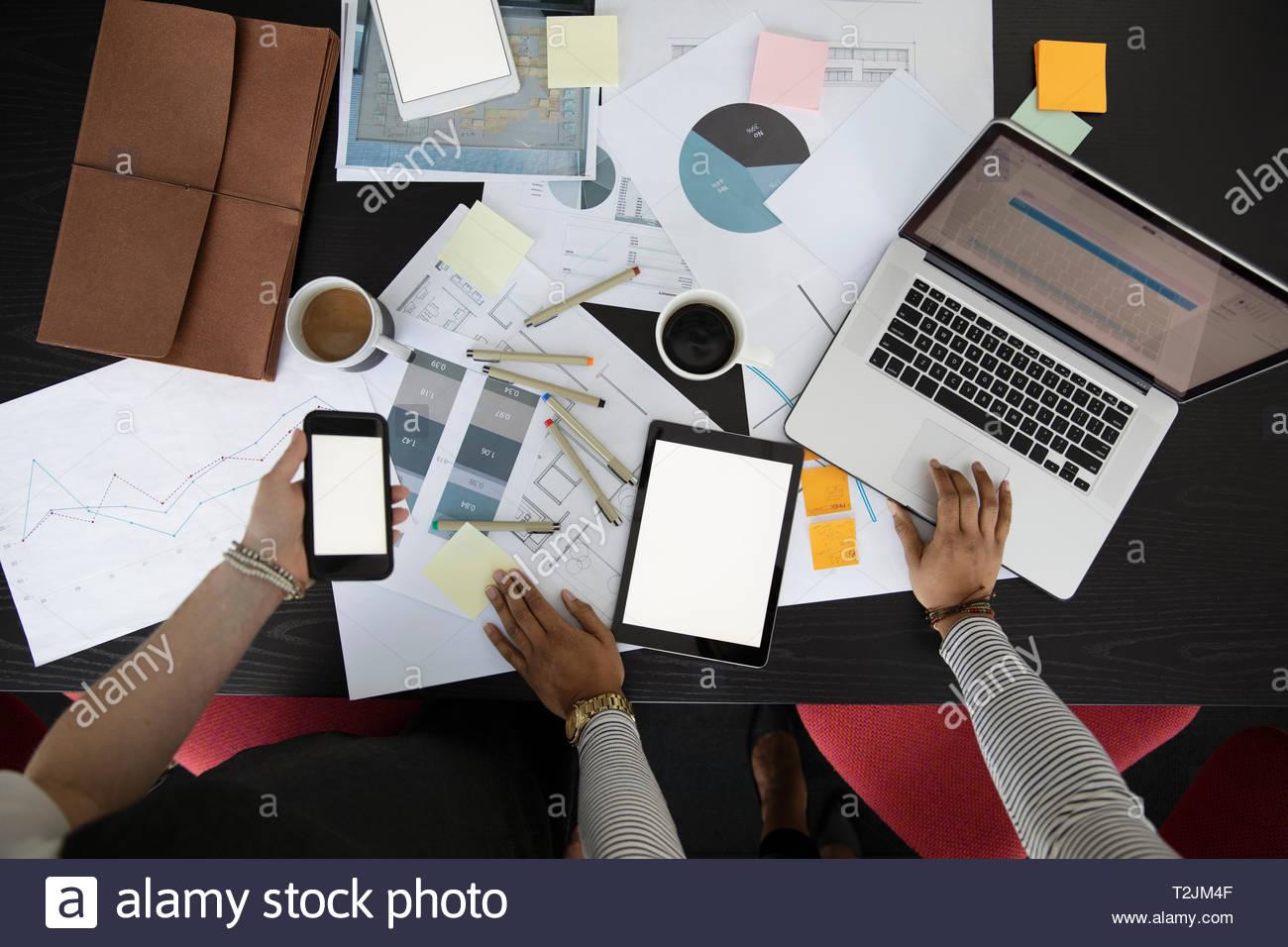 Vista da sopra la gente di affari strategizing, utilizzando la tecnologia Immagini Stock