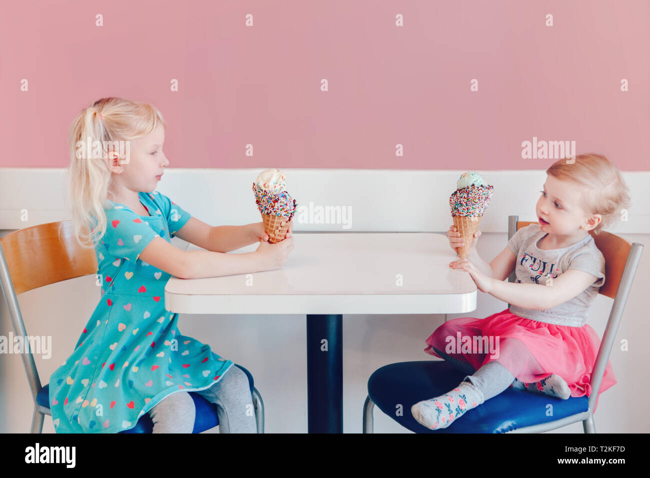 Stile di vita ritratto di due felice Caucasian carino adorabili bambini divertenti ragazze seduti insieme la vanteria vantando il loro gelato. Amore invidia gelosa sis Immagini Stock