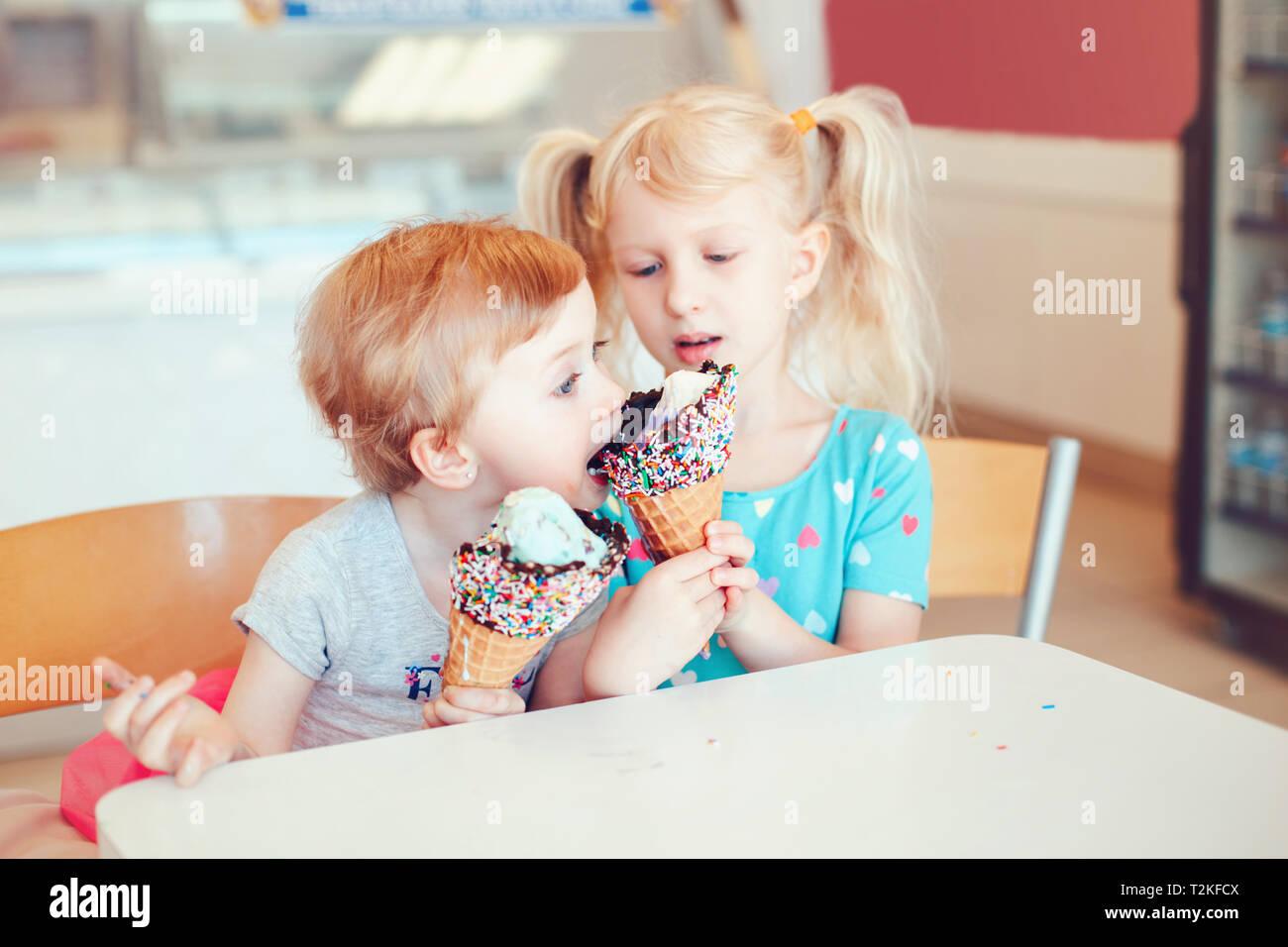Stile di vita ritratto di due felice Caucasian carino adorabili bambini divertenti ragazze seduti insieme la condivisione di gelati. Amore sorelle amicizia concetto. Migliori Immagini Stock