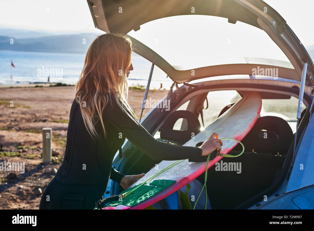 Giovane donna rimozione surfboard dal bagagliaio della vettura Foto Stock